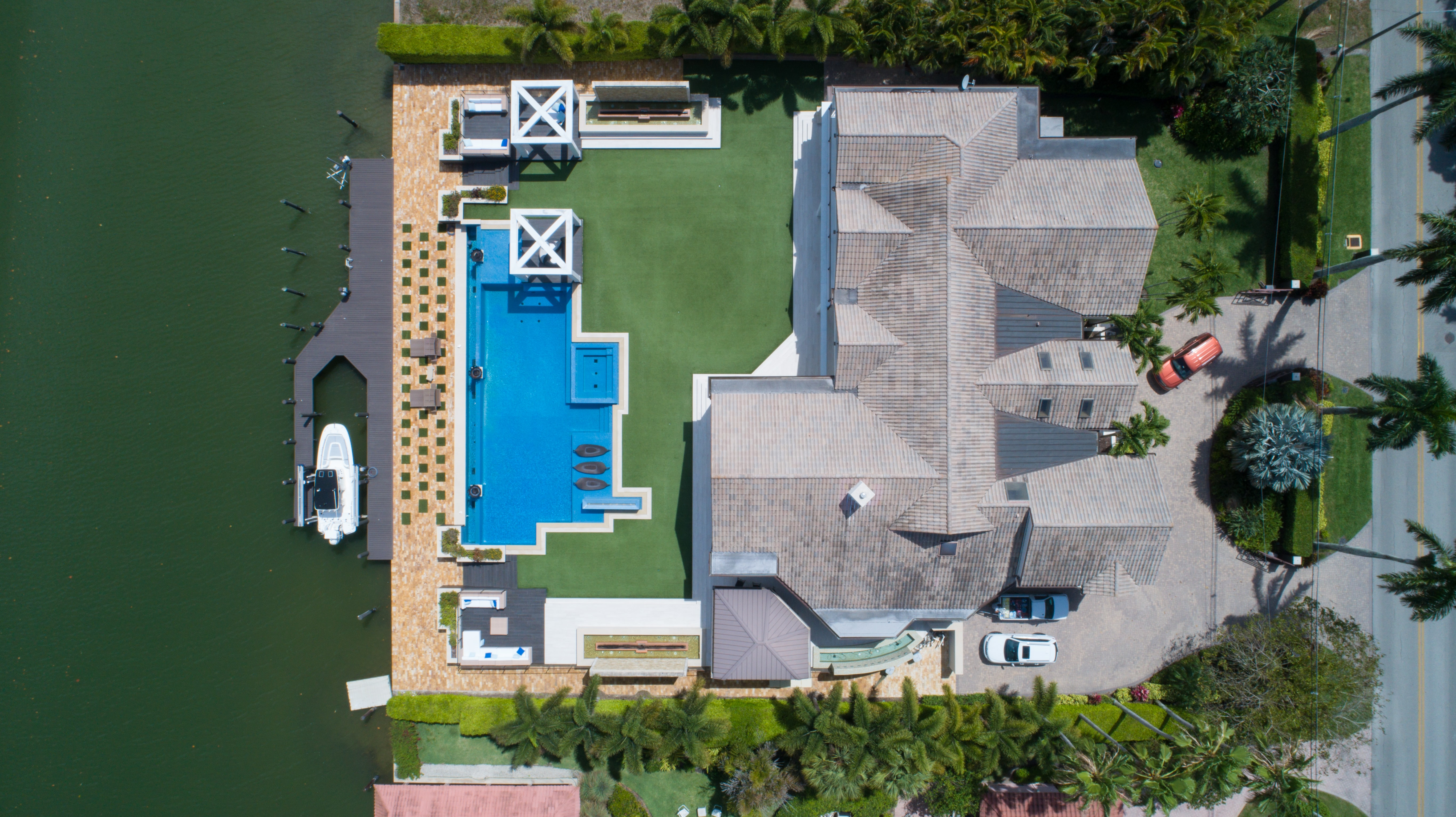 A drone shot of a mansion, boat, canal, pool, car, and driveway in Naples