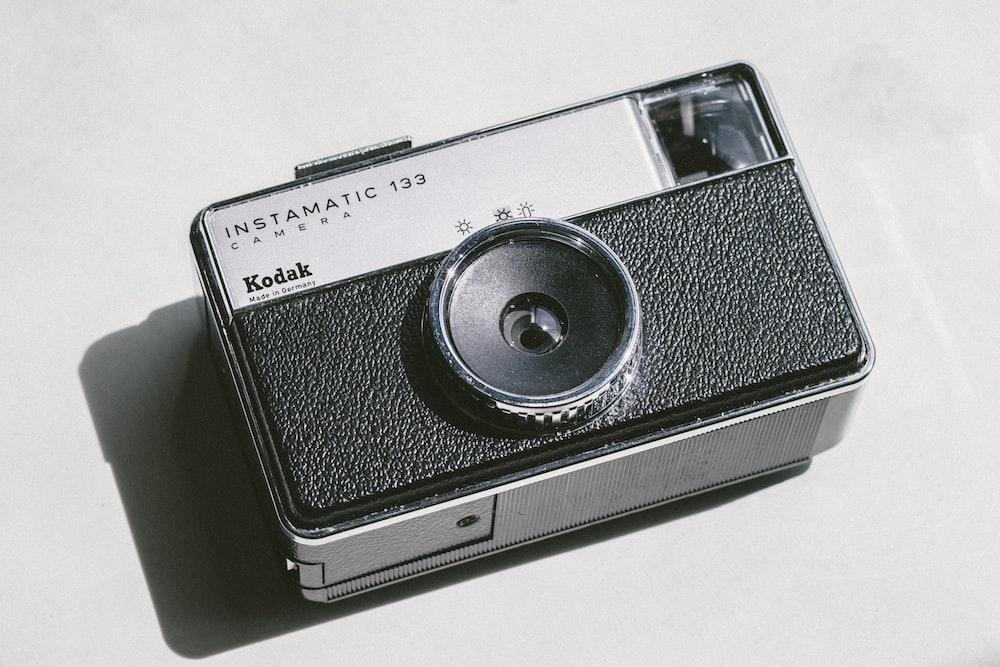 black and gray Kodak camera on white surface