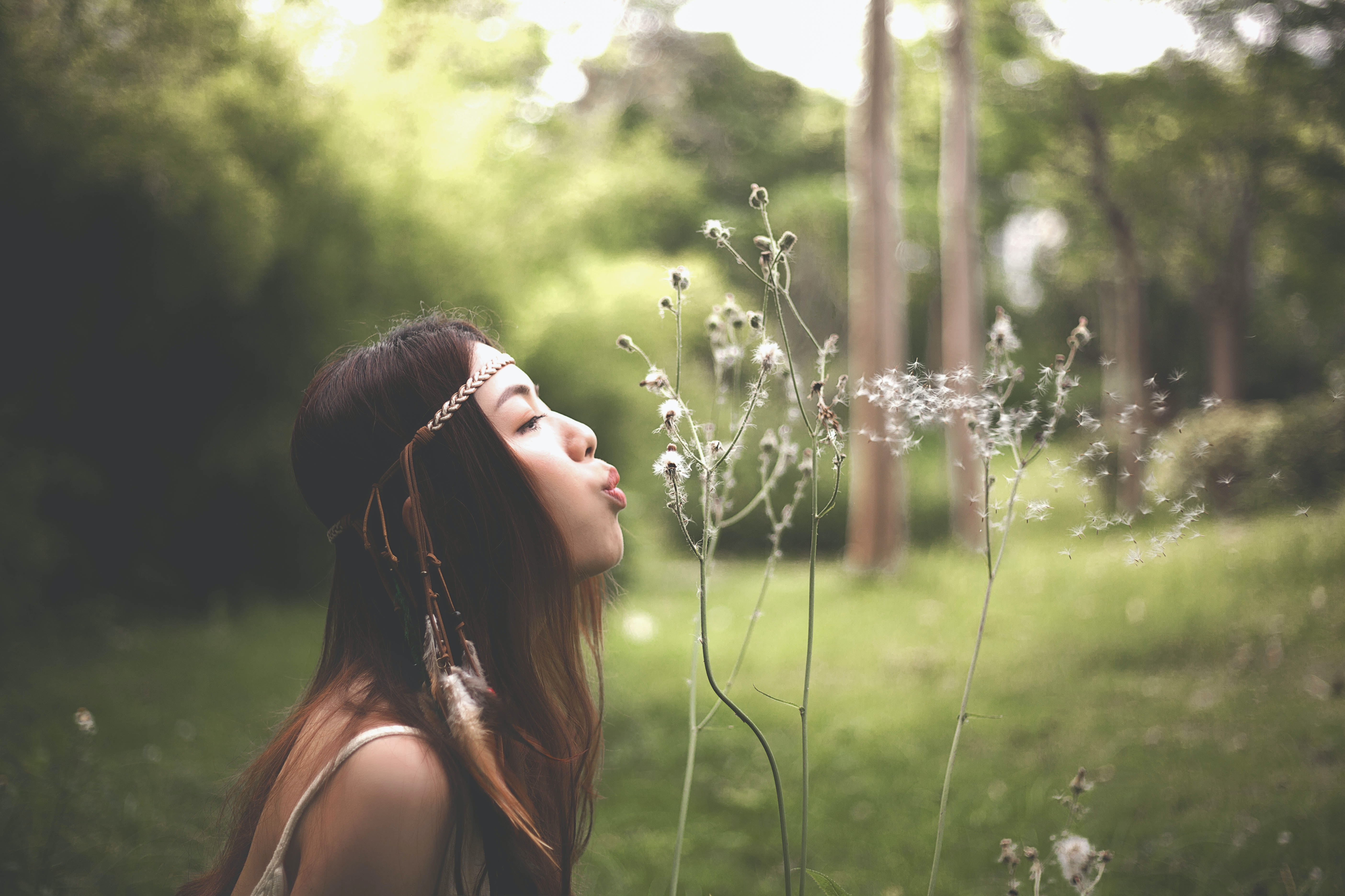 A young woman blowing on dandelion seed heads