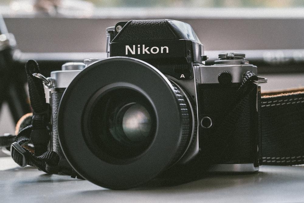 black Nikon milc camera on white panel