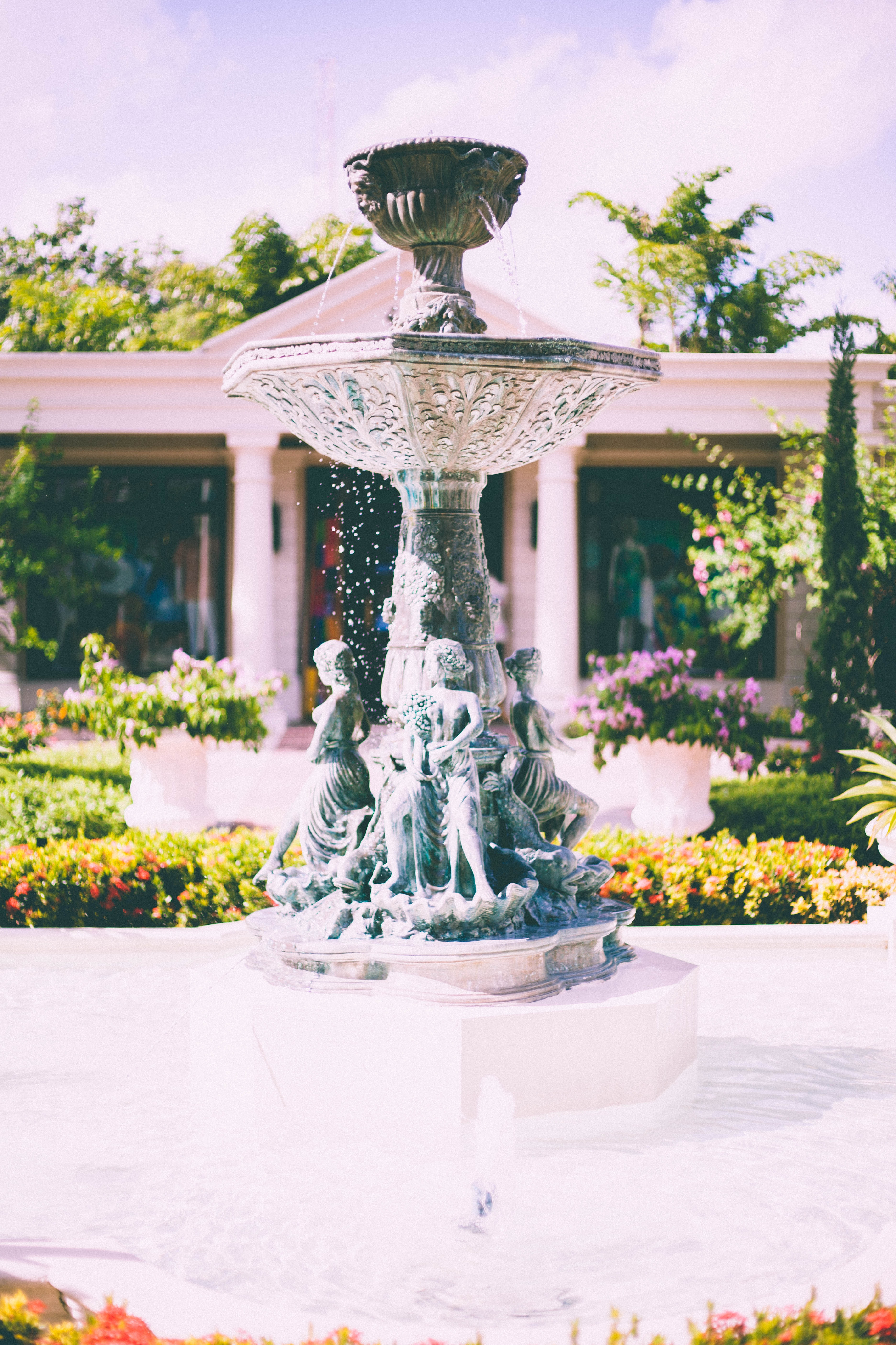 An ornate fountain in the middle of a garden in front of a classical building