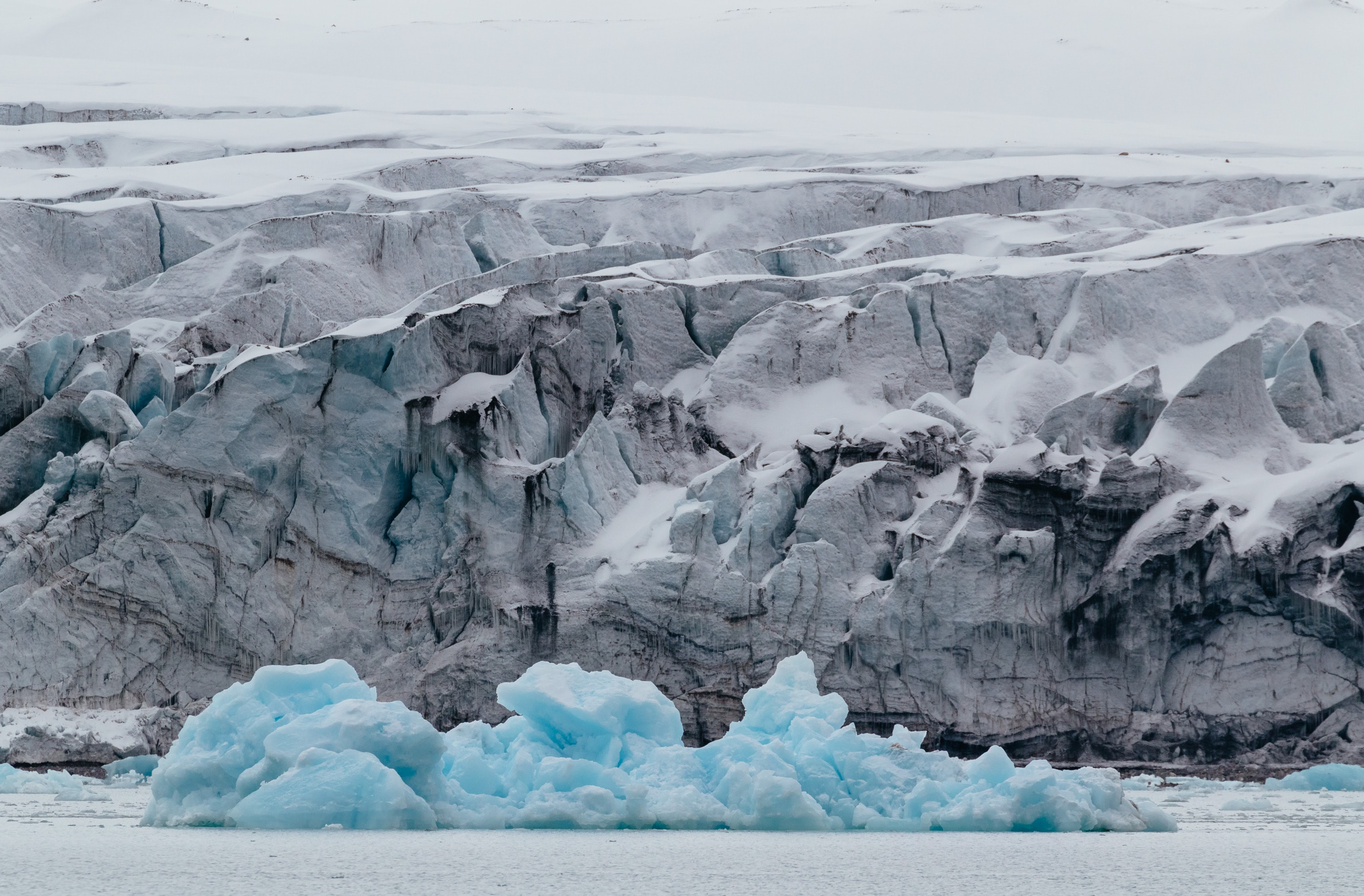 Ice glaciers in the water and snow covered rock formations in the background in Svalbard