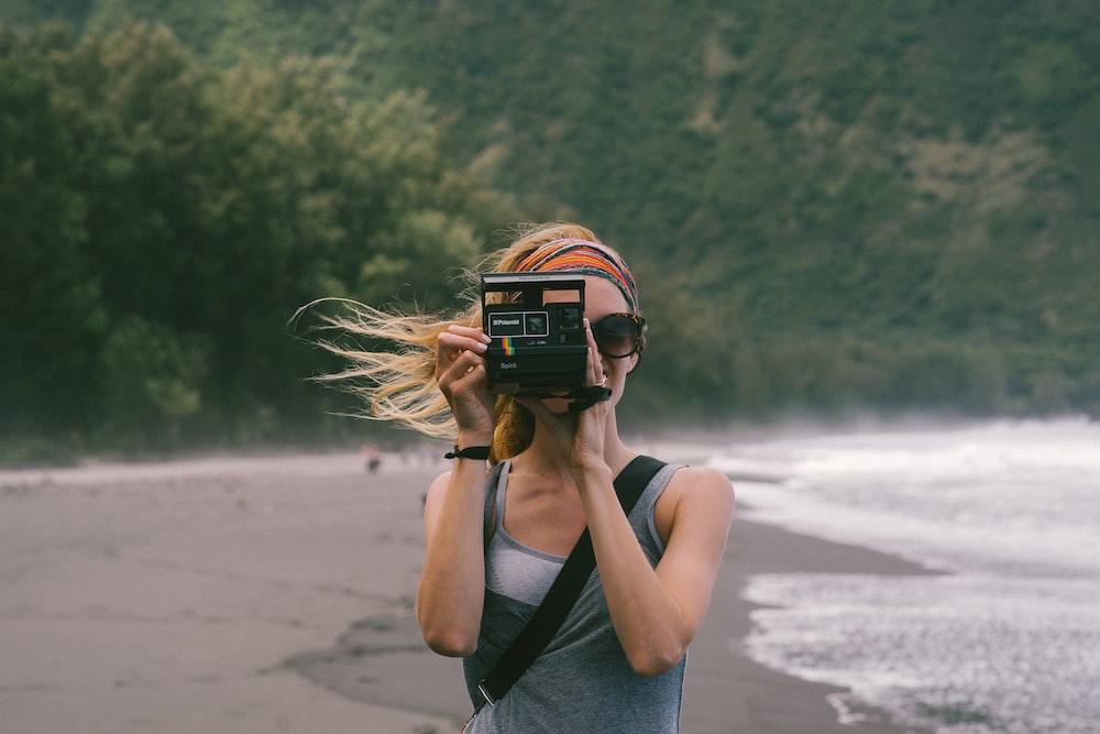 woman standing near seashore taking photo