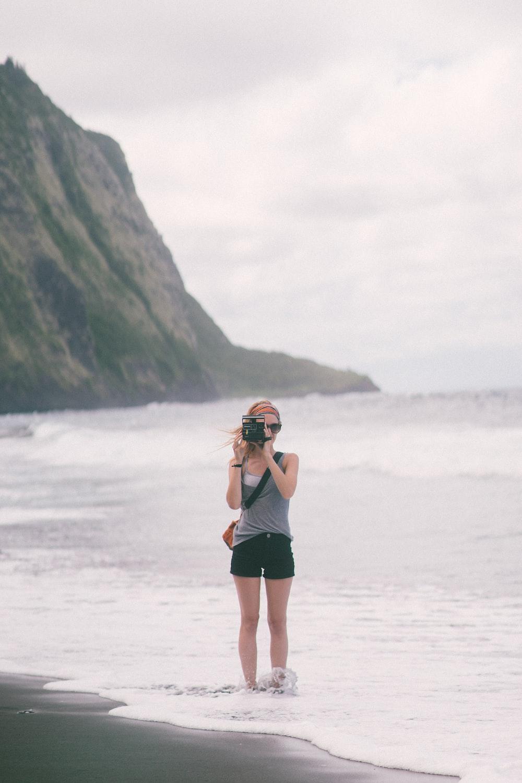 woman holding camera standing on beach