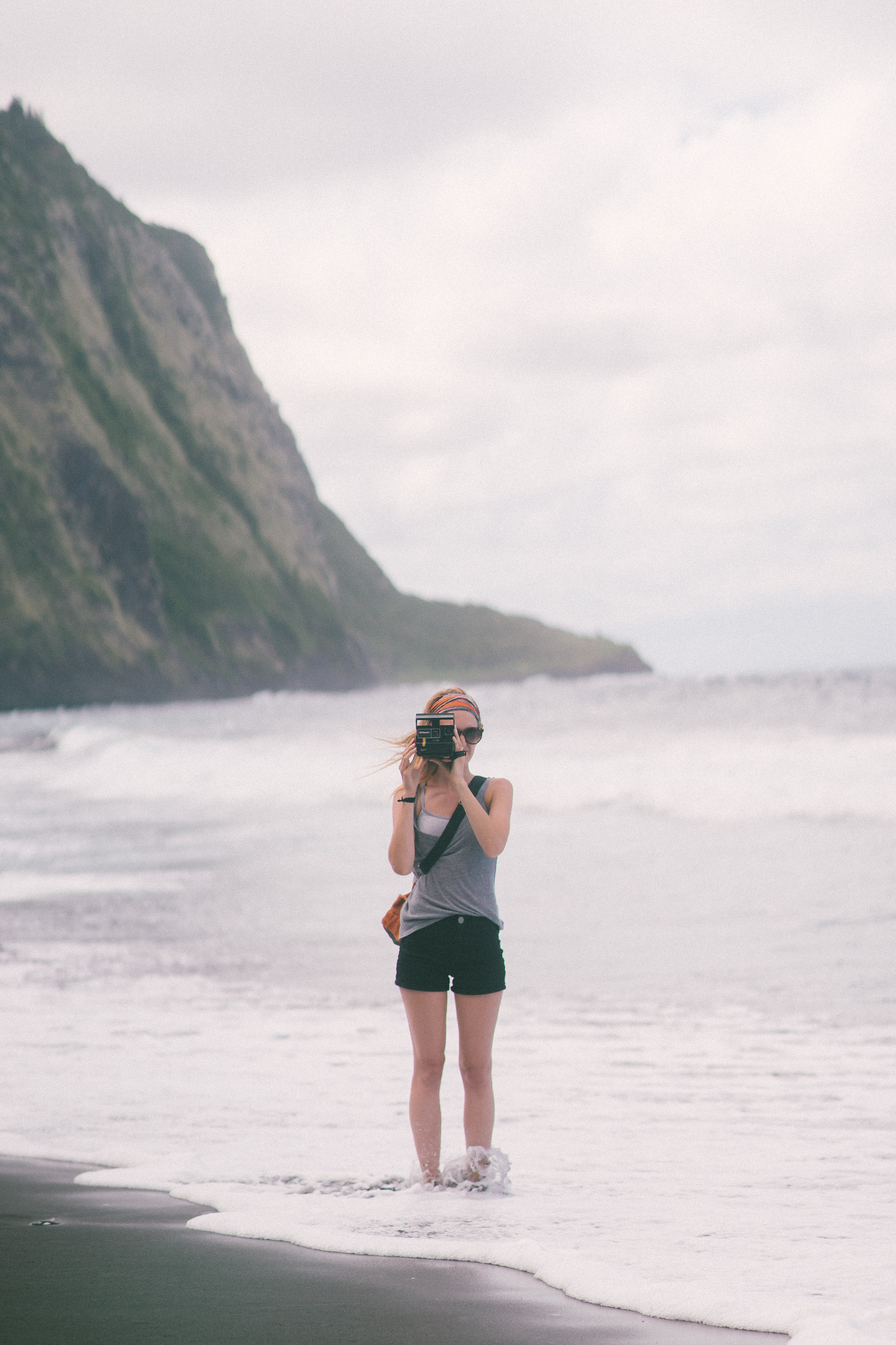 Young woman standing on the beach and taking a photo with a Polaroid camera