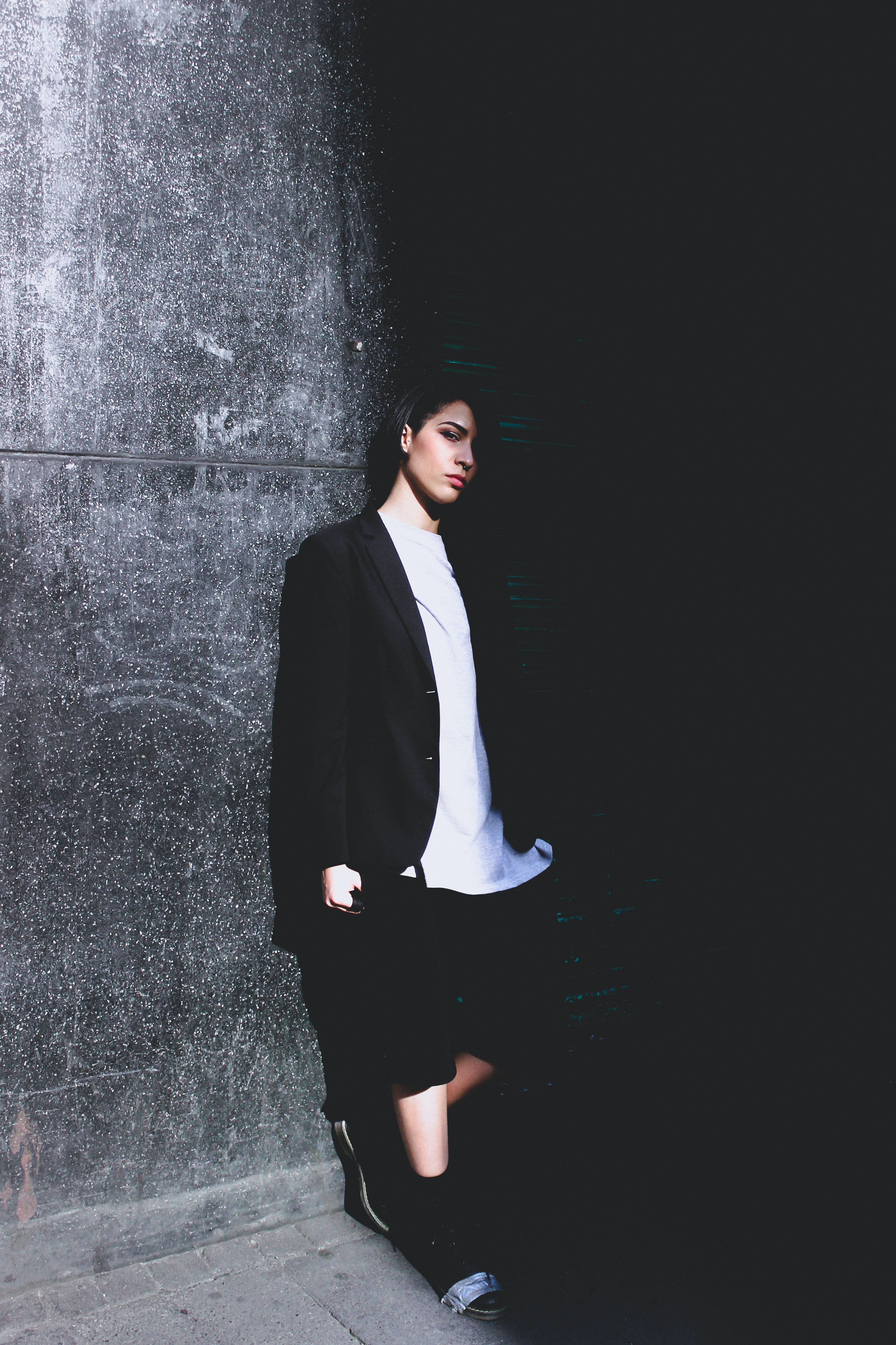 Person in business casual clothes leaning against a wall in partial shadow