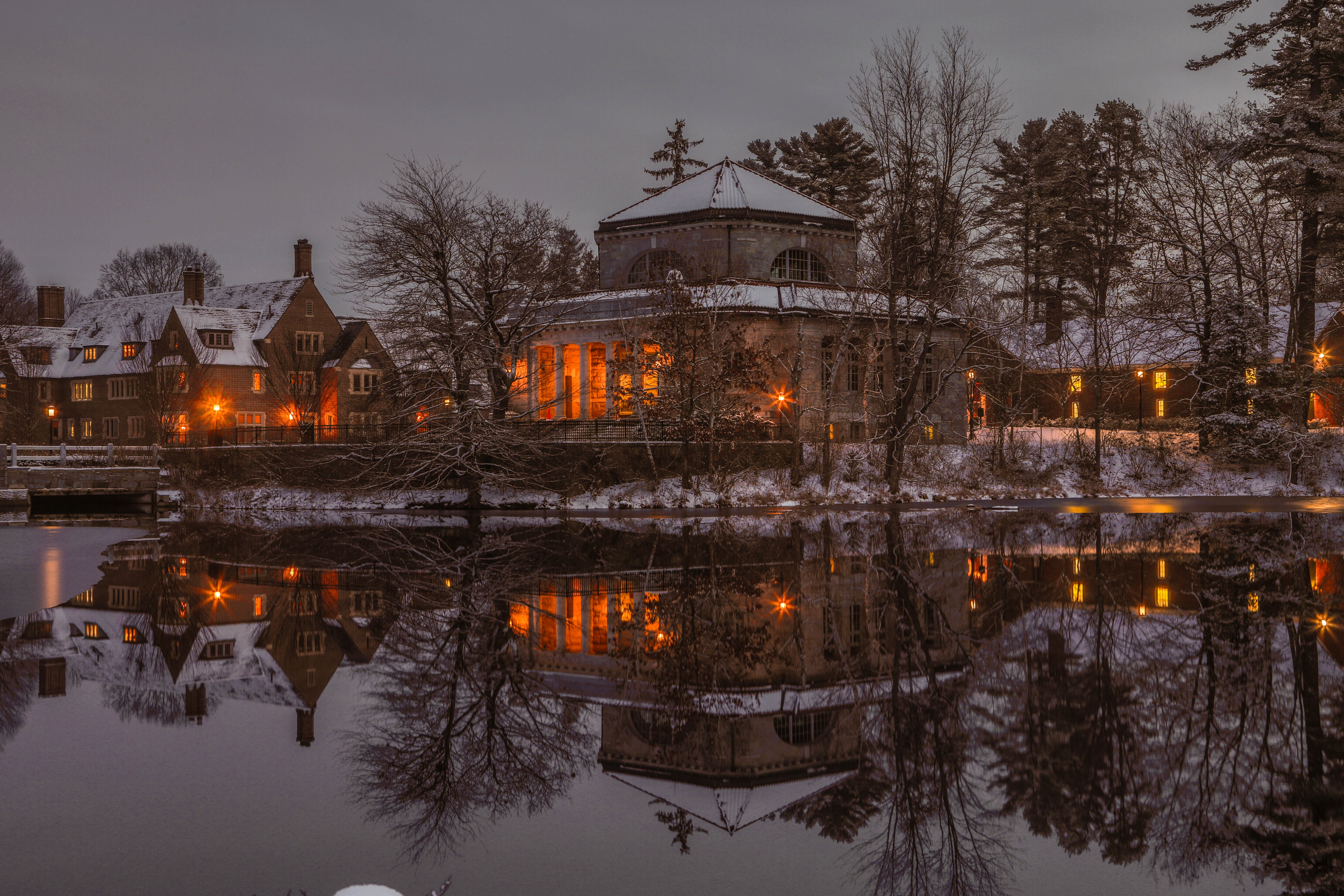 Snowy lake showing reflection of lit up campus, St. Paul's School