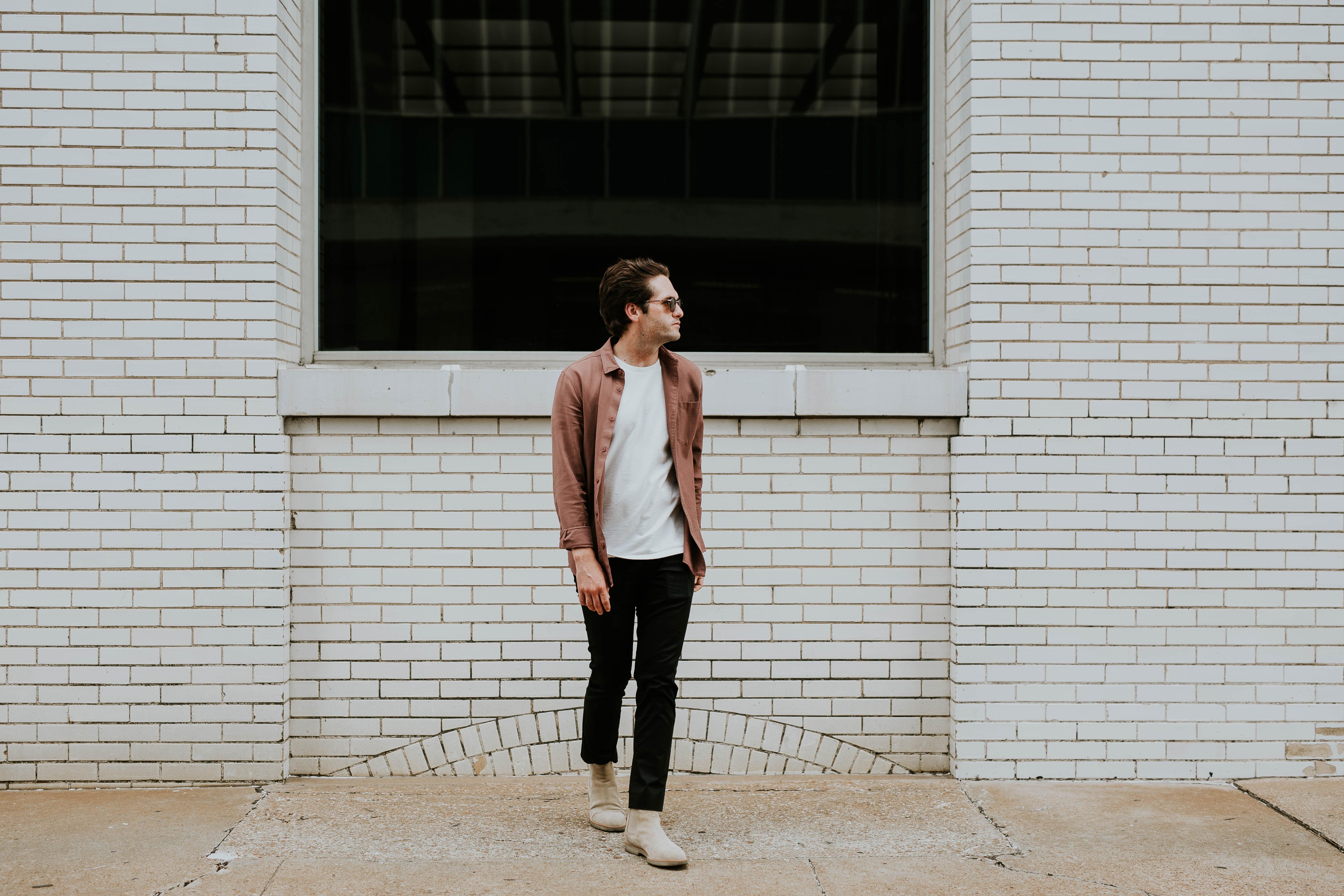 man standing beside beige brick wall