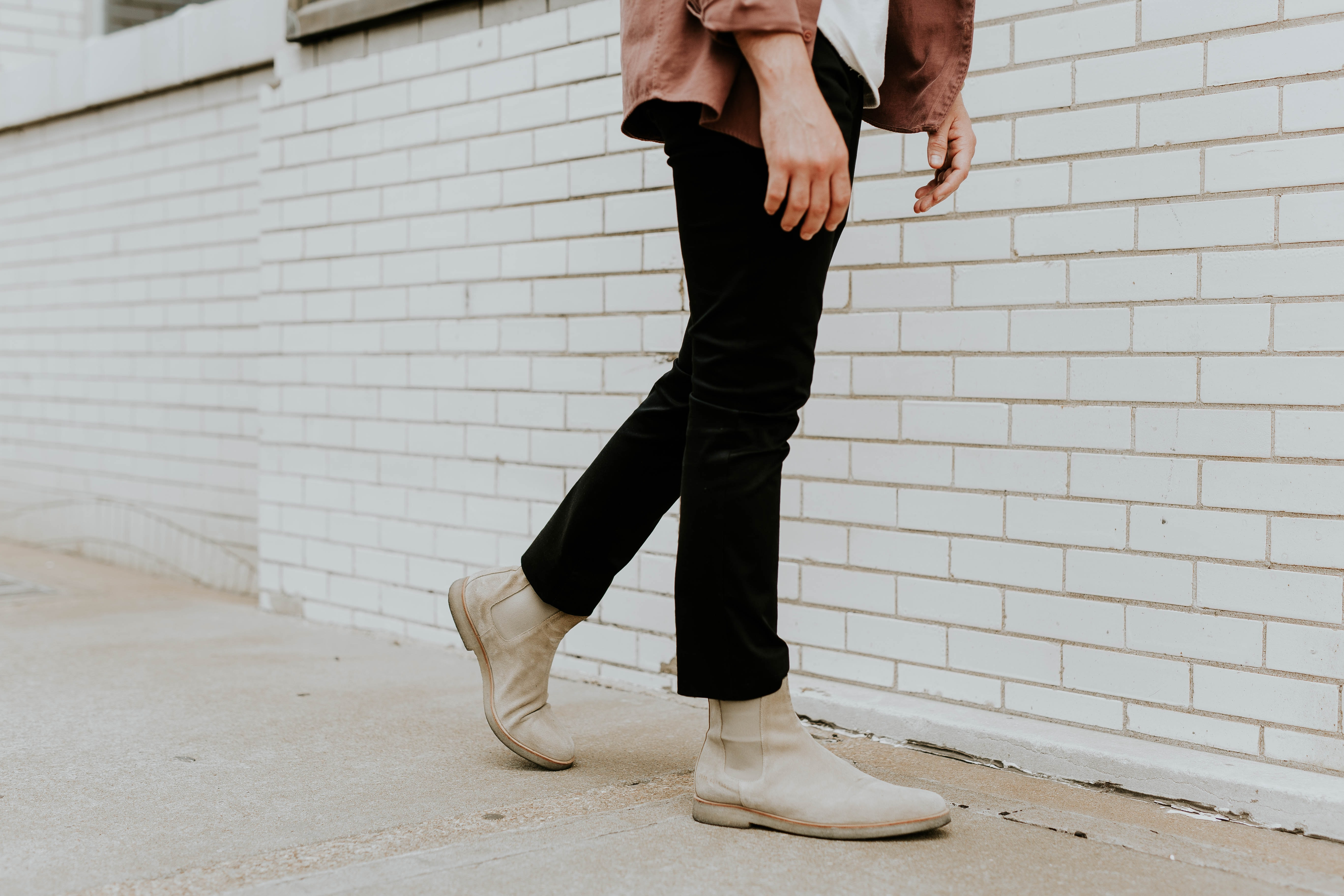 person wearing white leather chelsea booties and black pants