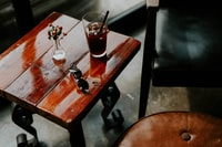 drinking glass and sunglasses placed on square brown side table