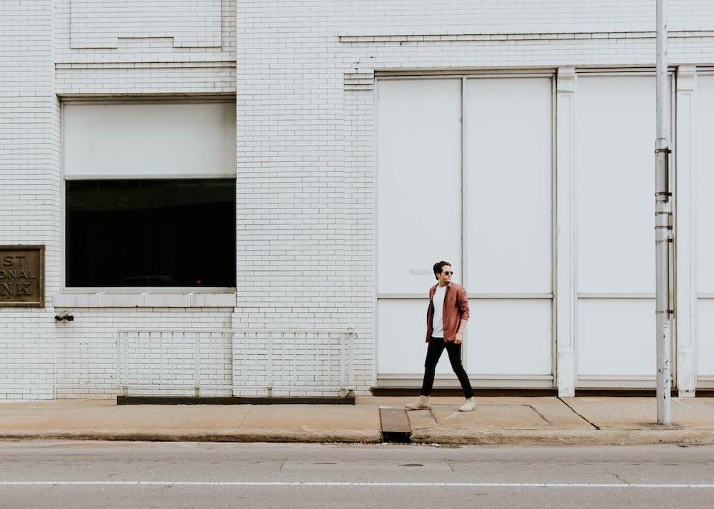 man walking on sidewalk beside white building during daytime