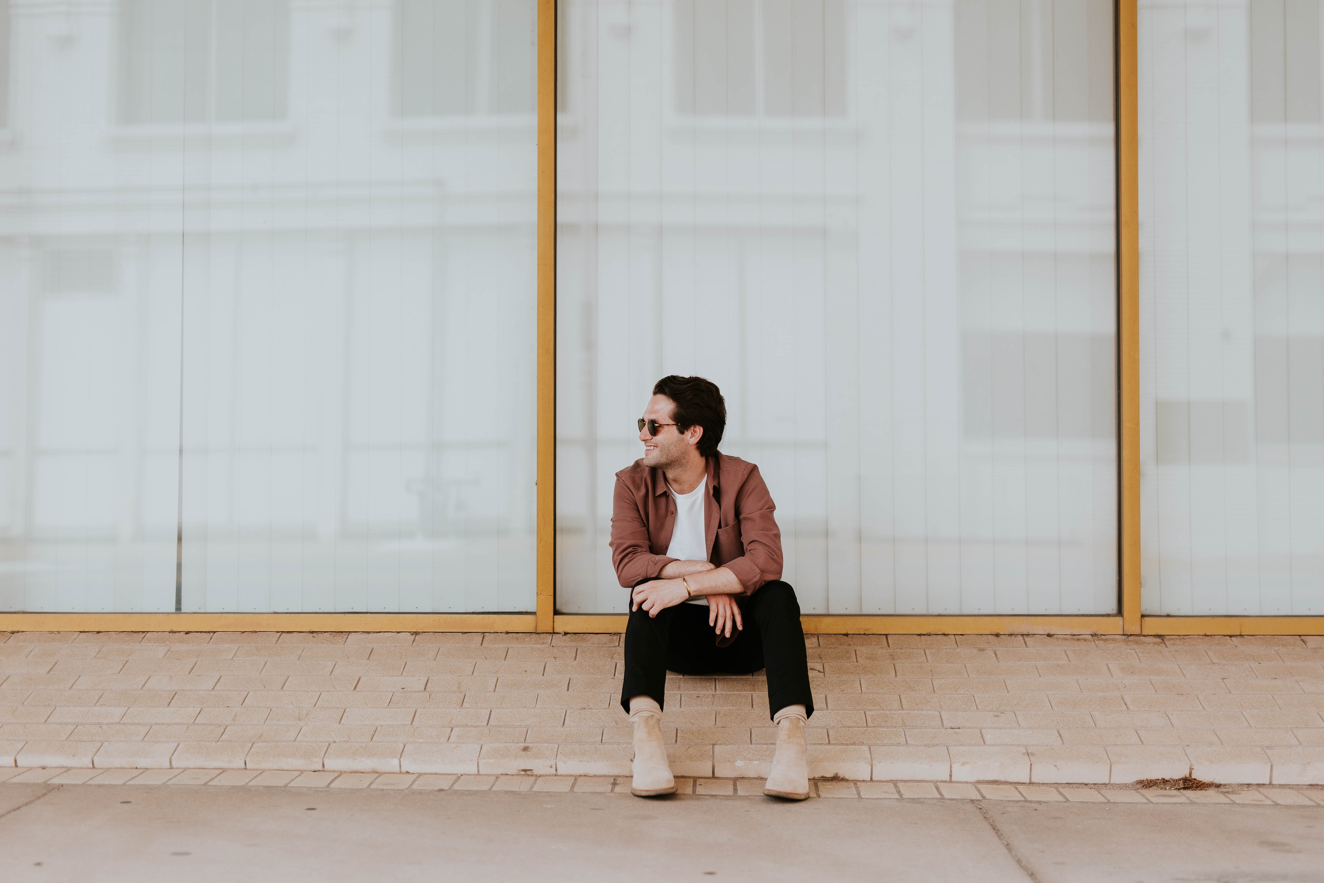 photo of man sitting on brown bricks against glass wall