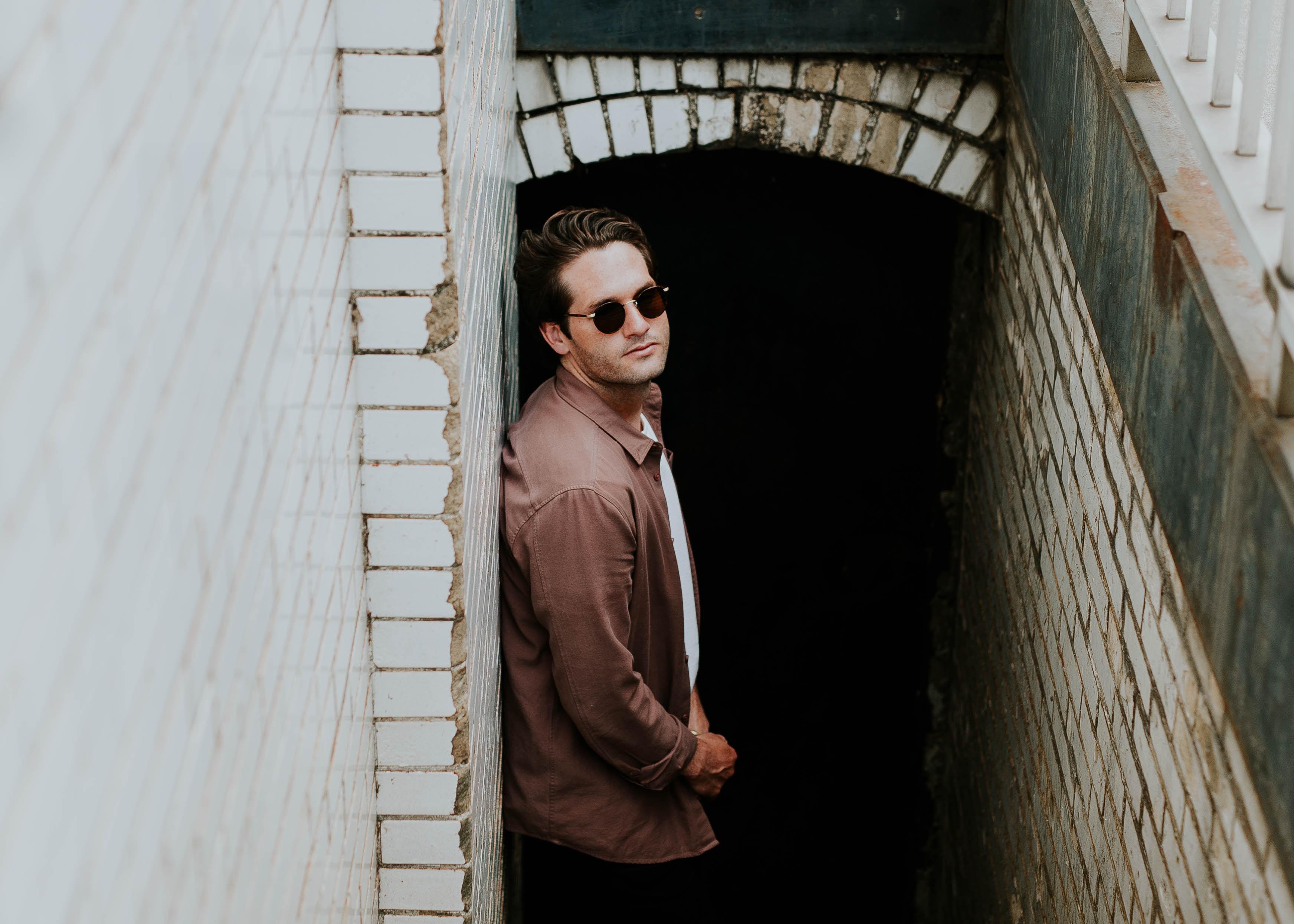 man leaning on beige wall near hallway