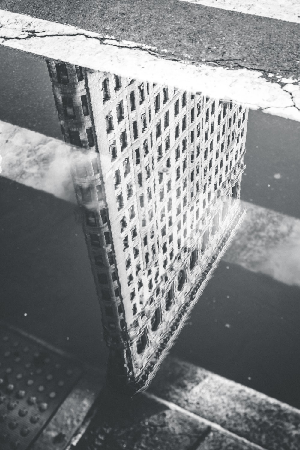 grayscale photography of reflection of building on body of water