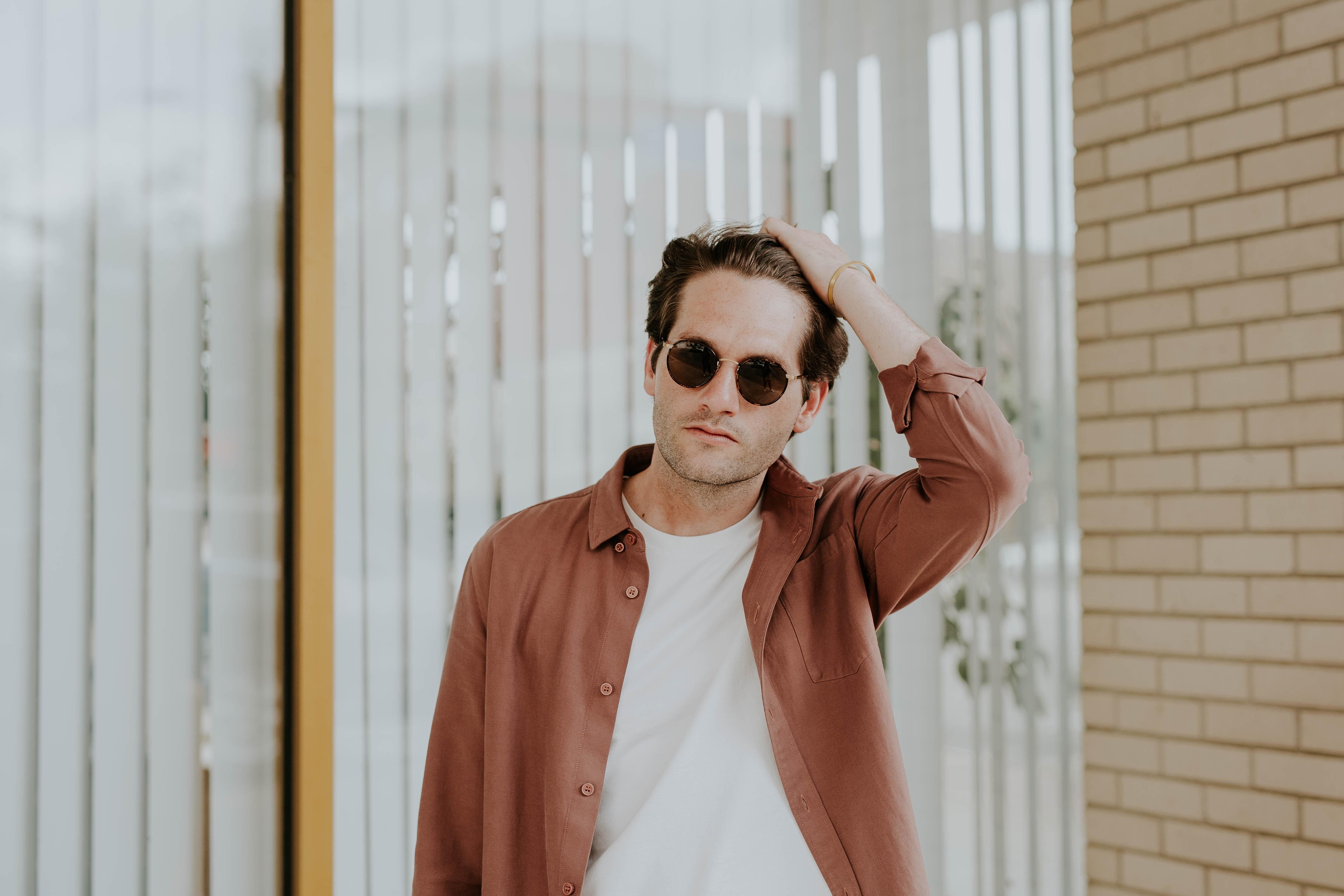 man in brown jacket near window blinds