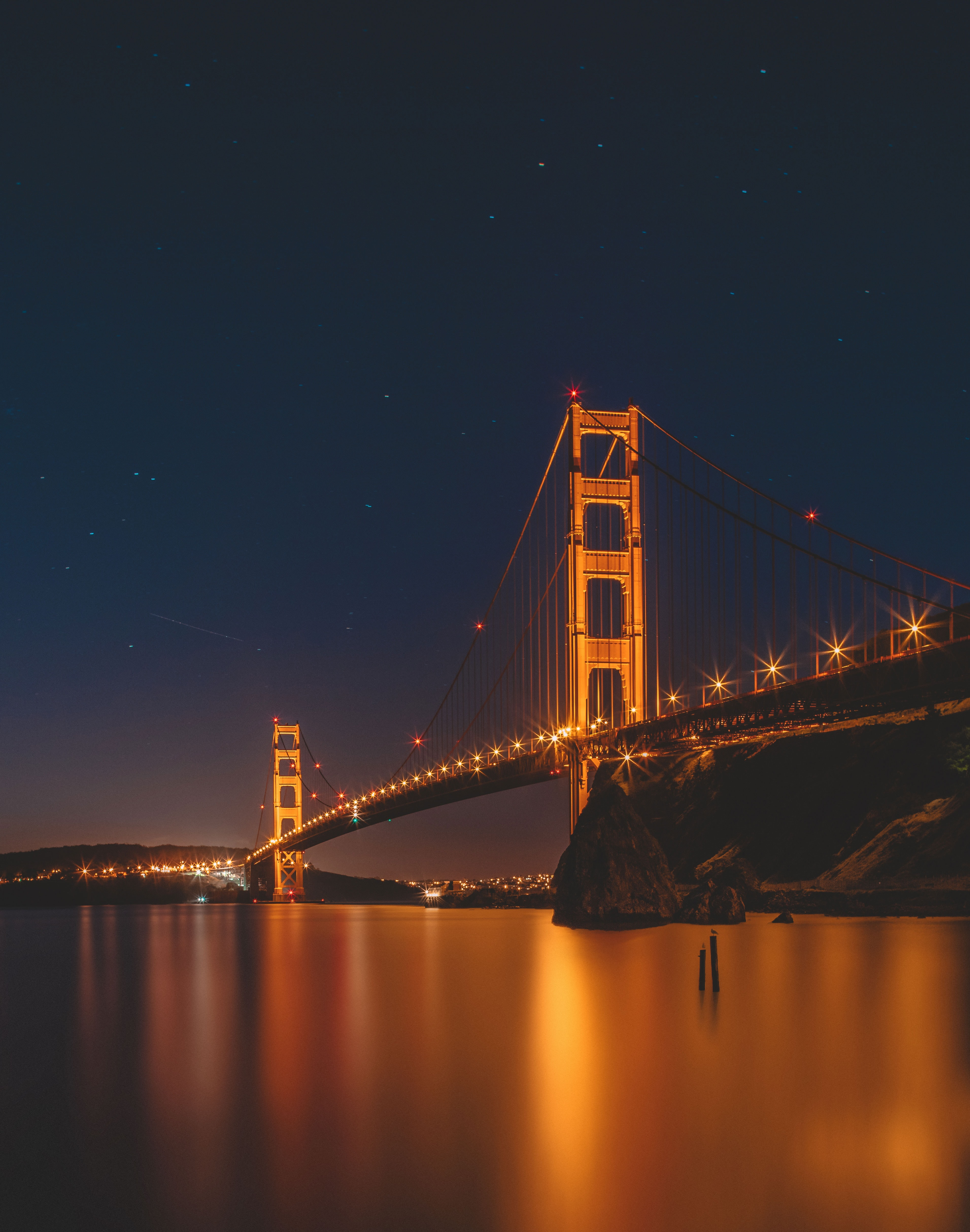 A picturesque shot of San Francisco Golden Gate Bridge with lights reflecting in water below