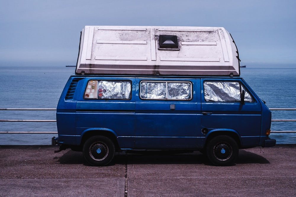 Blue Van With Window Protectors And A Container On The Roof