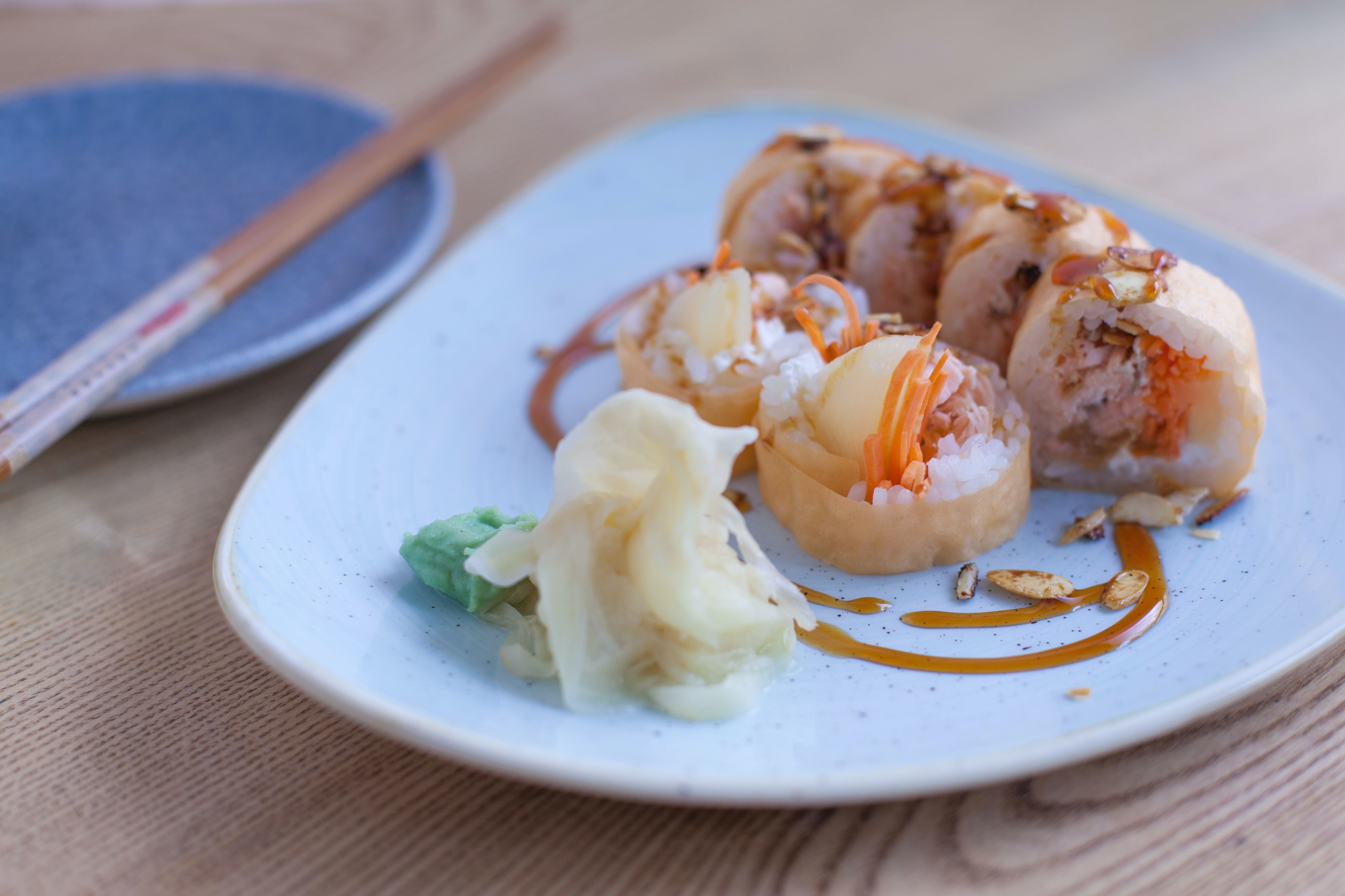 A plate of sushi with caramel colored sauce.