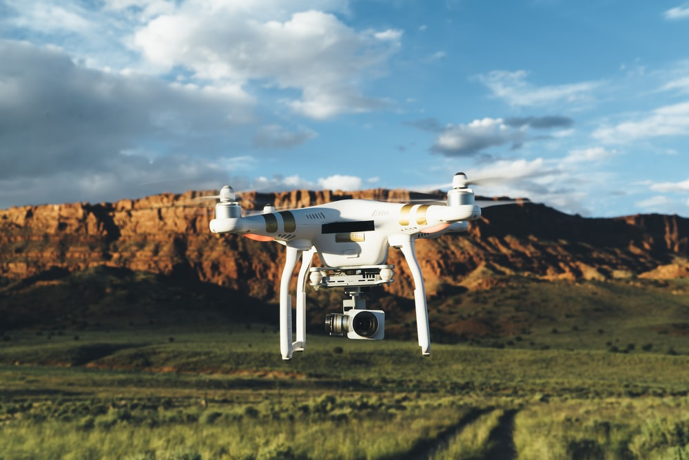landscape photography of DJI Phantom flying midair in front of mountain