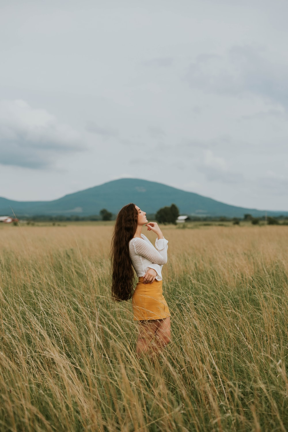 woman standing in the middle of grass field