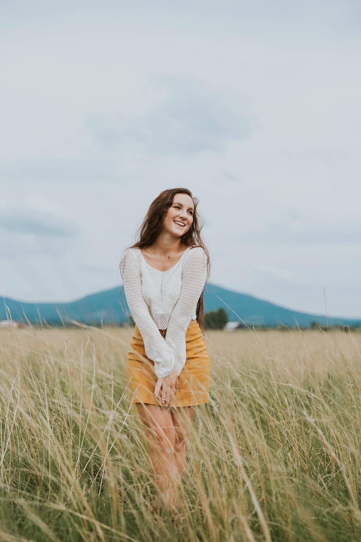 woman wearing brown long-sleeved shirt on green grass field