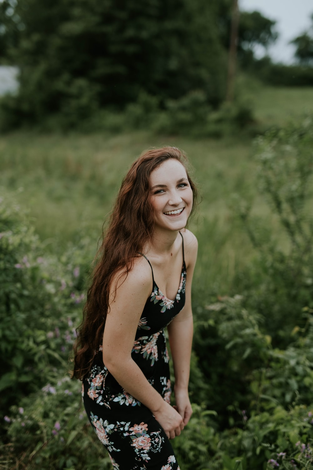 shallow focus photography of woman posing and smiling at camera