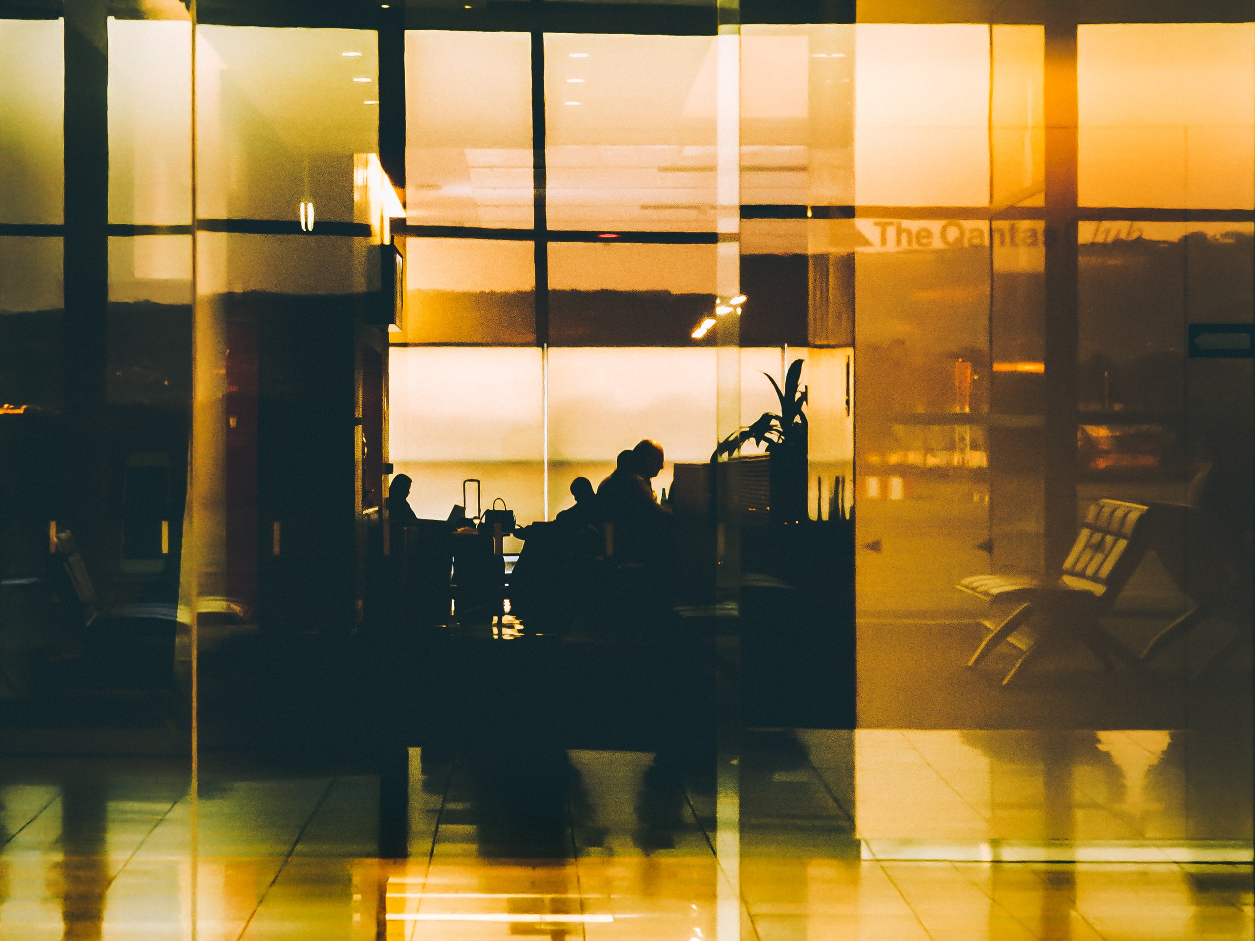 A fuzzy shot of silhouettes of people reflected in a glossy wall at the Adelaide Airport