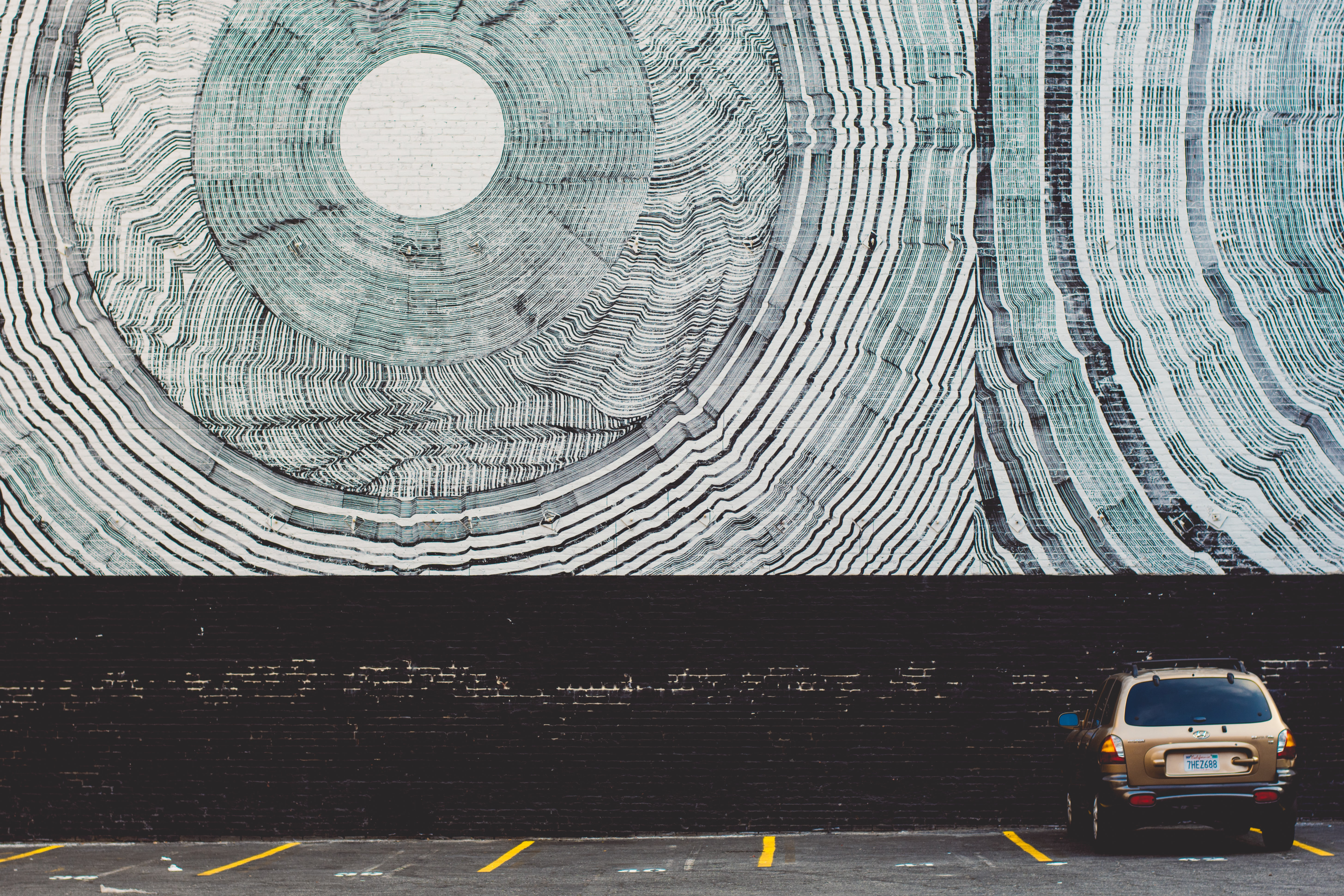 Mural in a Los Angeles with single car parked in parking lot