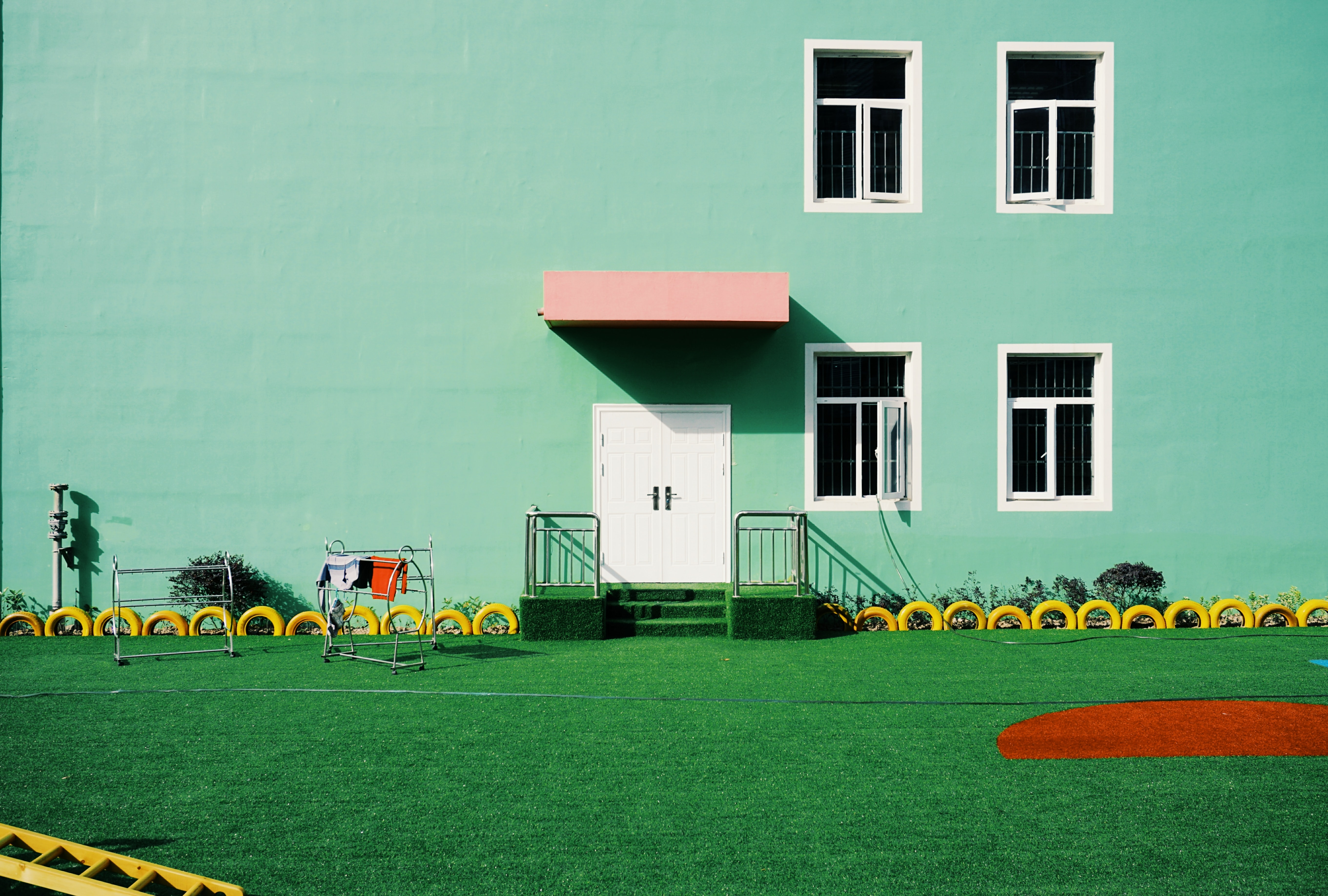 green painted building beside lawn