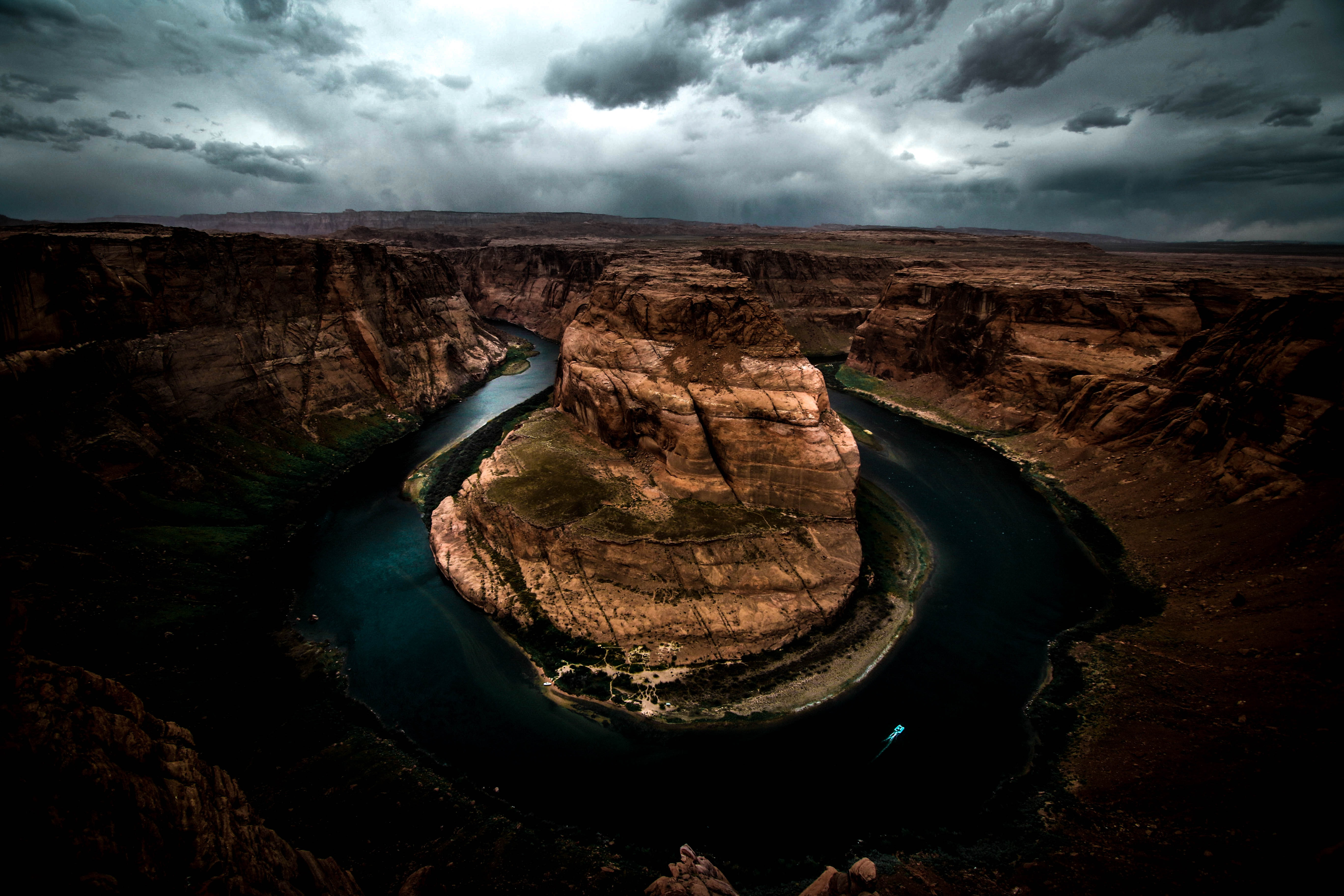 A dim shot of a horseshoe-shaped river bend in a canyon under a stormy sky