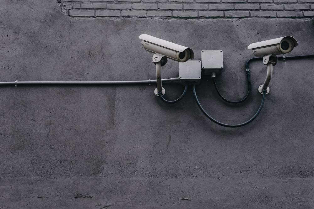 two bullet surveillance cameras attached on wall