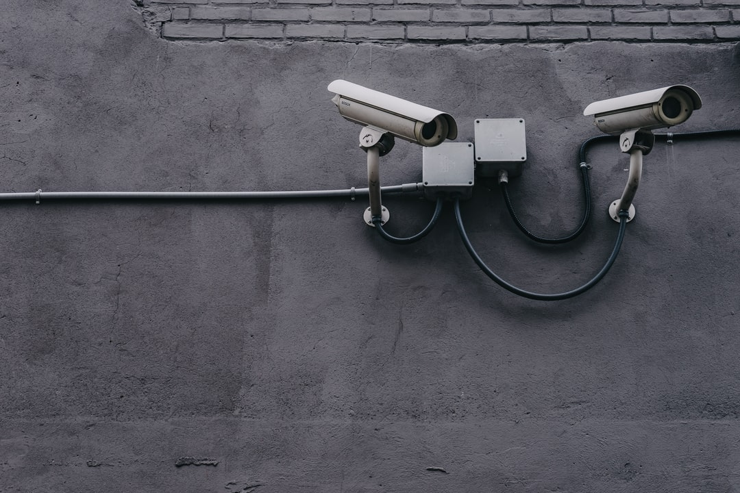 Two CCTV cameras on a gray wall