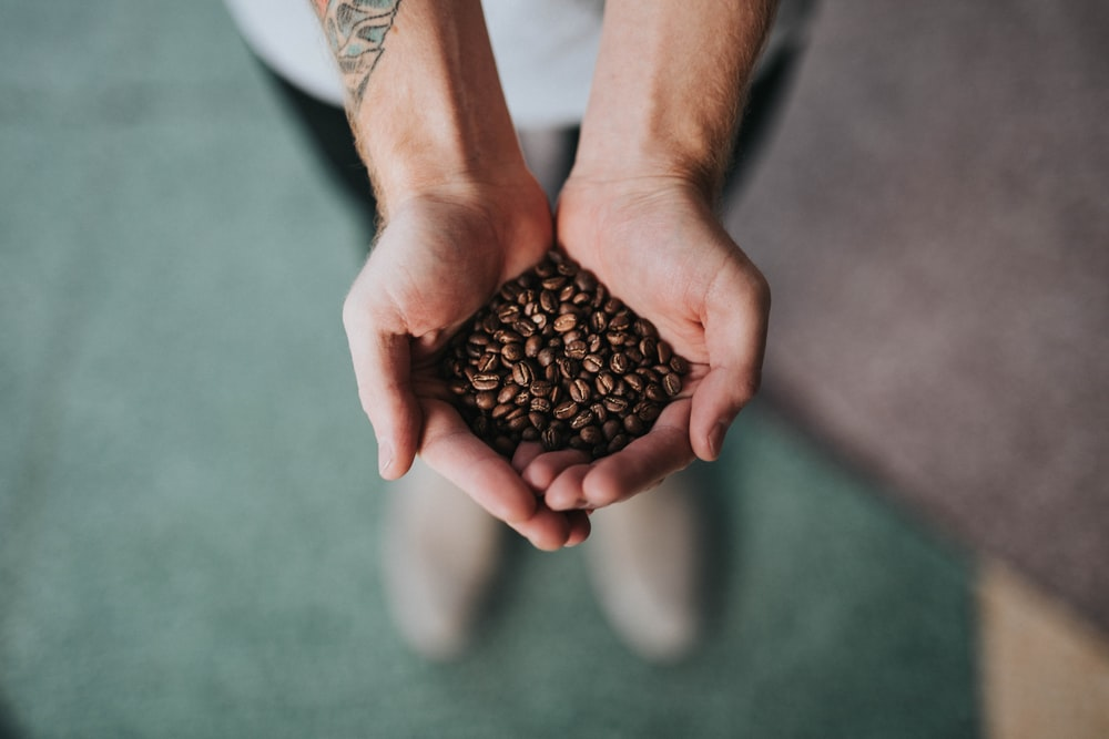 A person with a tattoo on his arm holding coffee beans in his hands