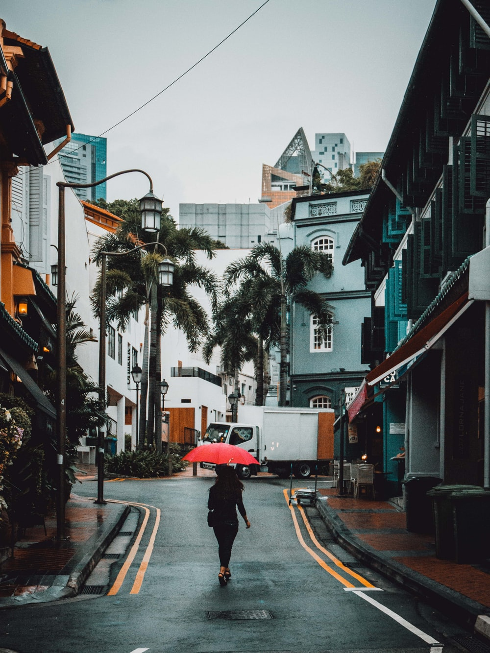 woman holding red umbrella walking on road between buildings at daytime