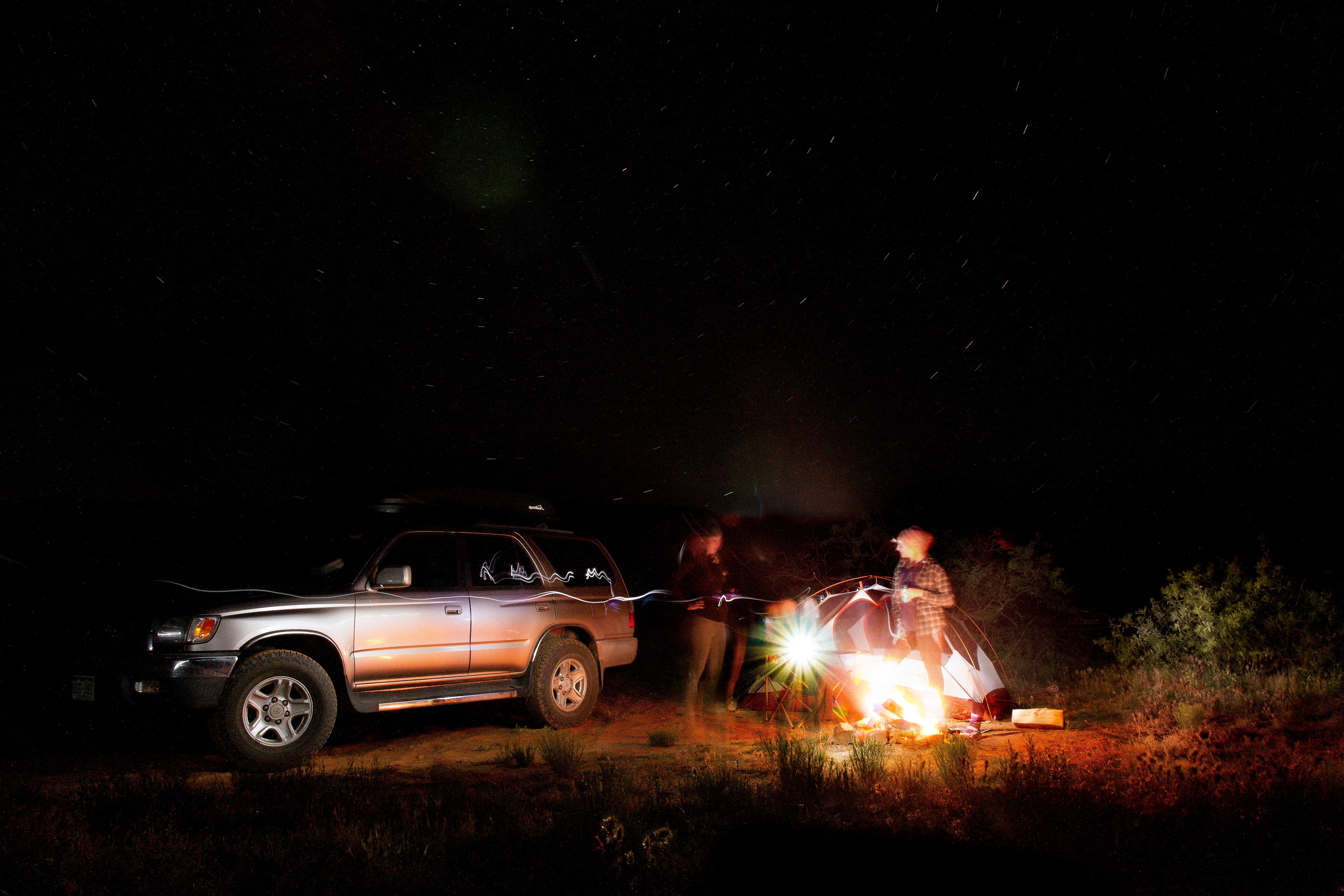 Long exposure photo of people at night by the SUV and the tent camping in Sedona.