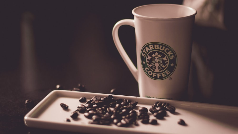 coffee beans beside Starbucks coffee mug