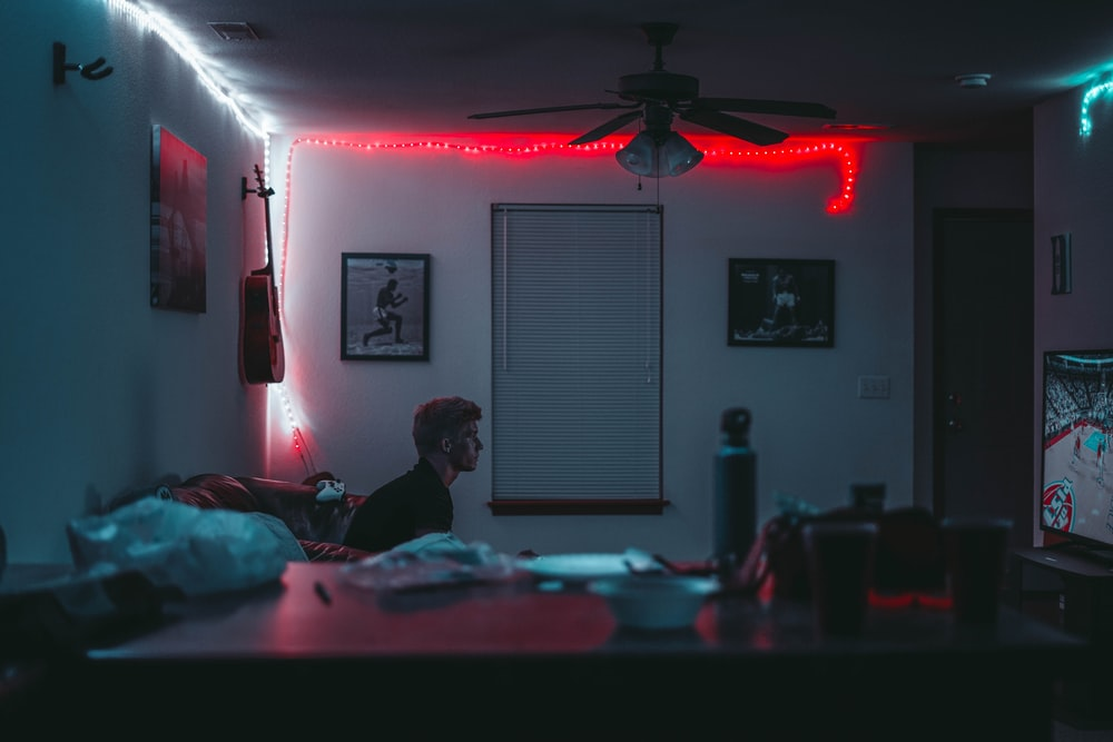 man sitting inside room near window blinds with lights turned on