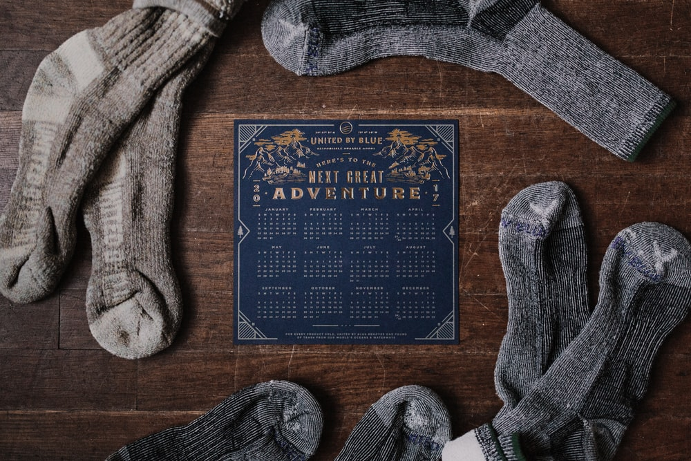 pair of gray socks and blue calendar on table