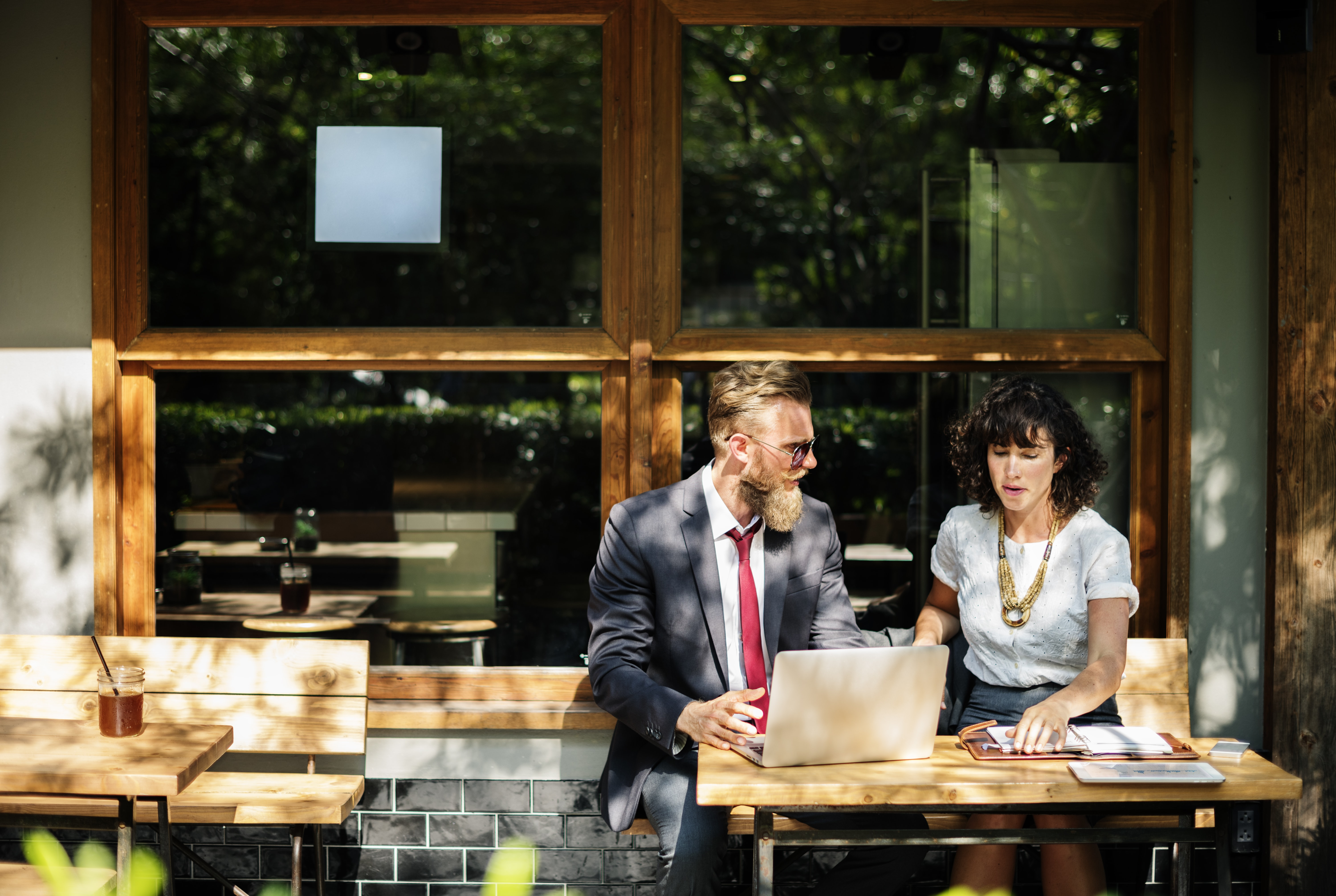 A man and a woman sitting together at a computer outside of a coffee shop for a business meeting