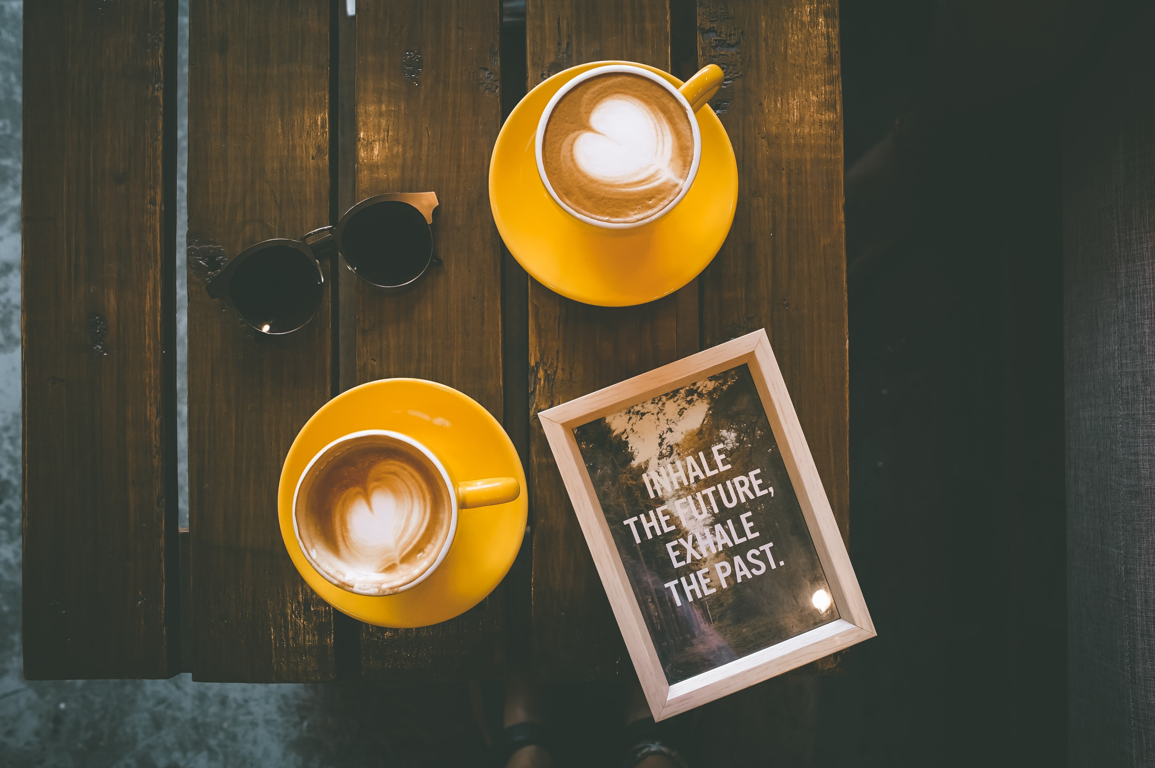 Two cups of latte coffee art on wooden table with print artwork and sunglasses, Cebu City