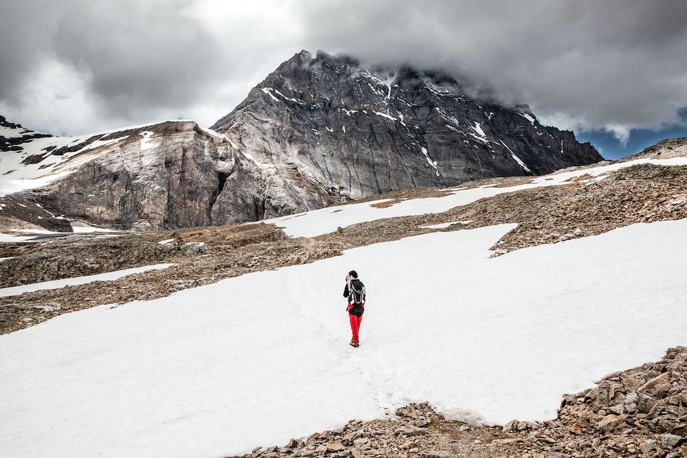 person walking on snow towards mountain