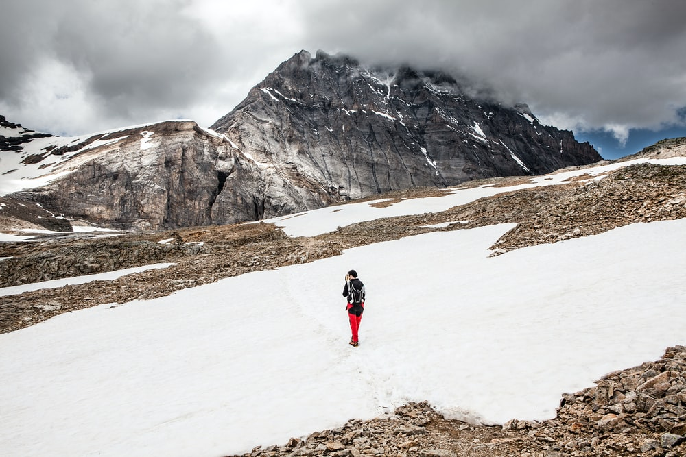 person walking on snow towards mountain