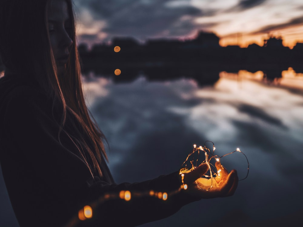woman holding string lights at dusk