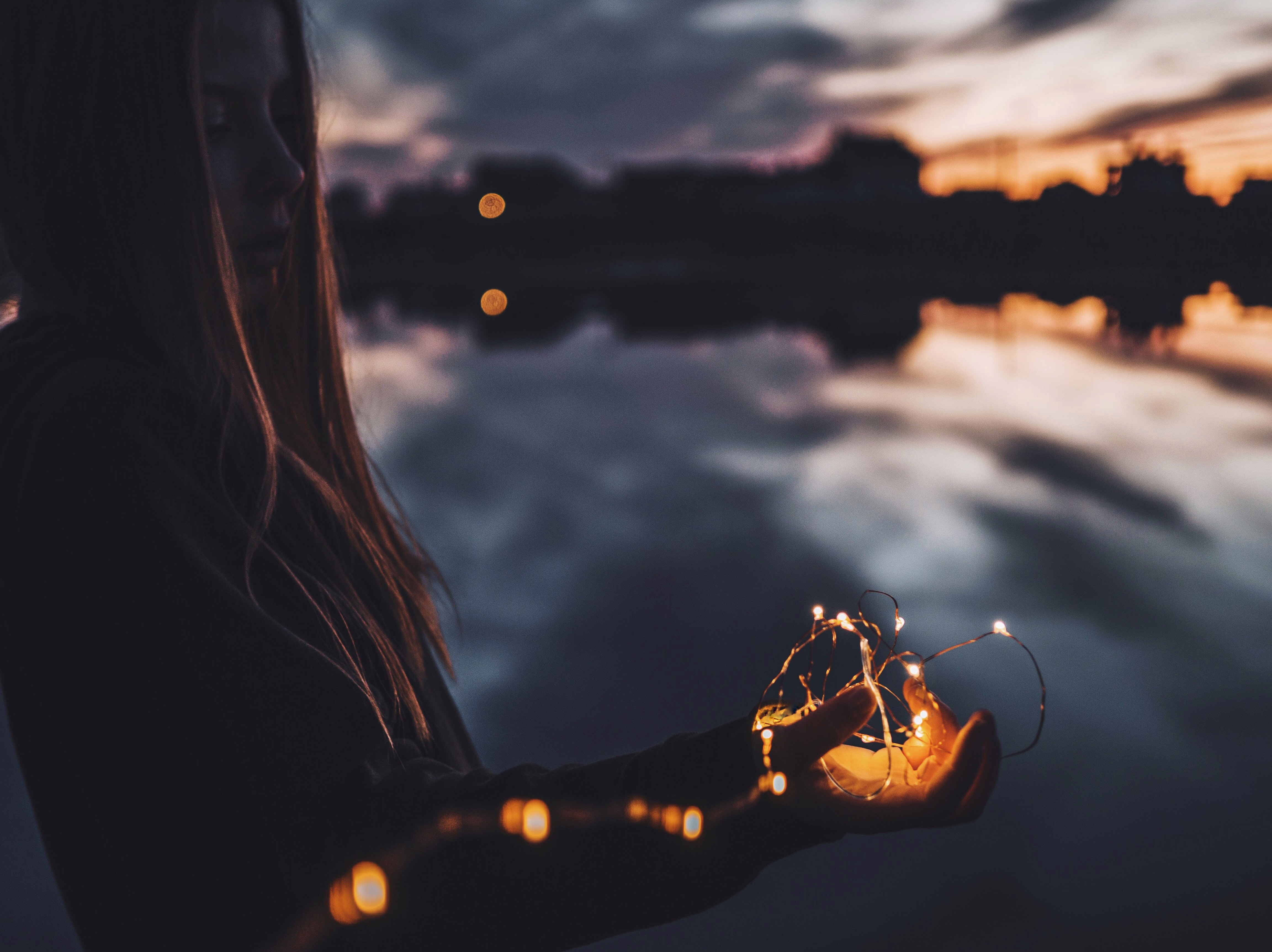 A girl holding fairy lights in her hand by a lake on an evening