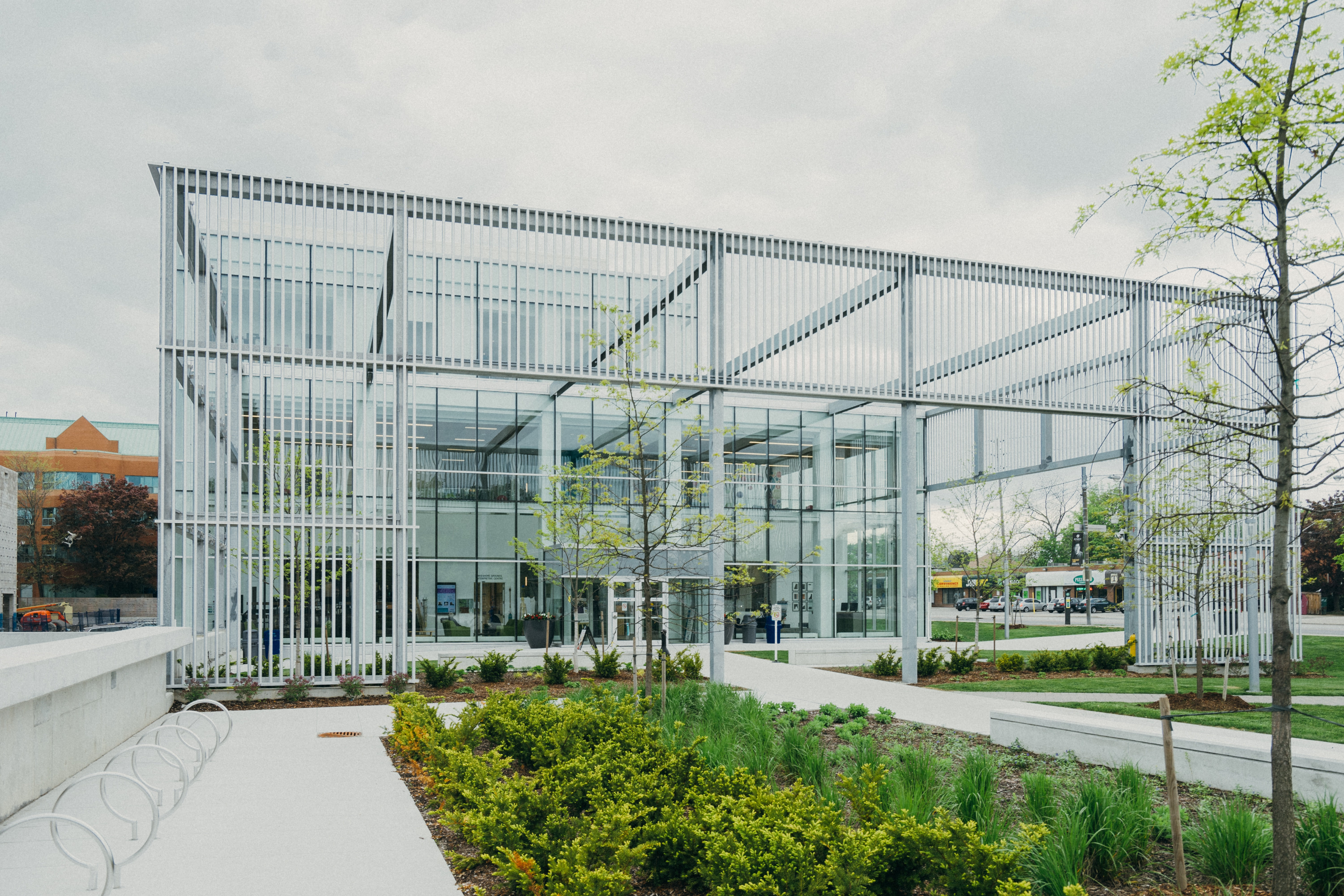 A flower bed near a metal structure with a glass building facade at the back