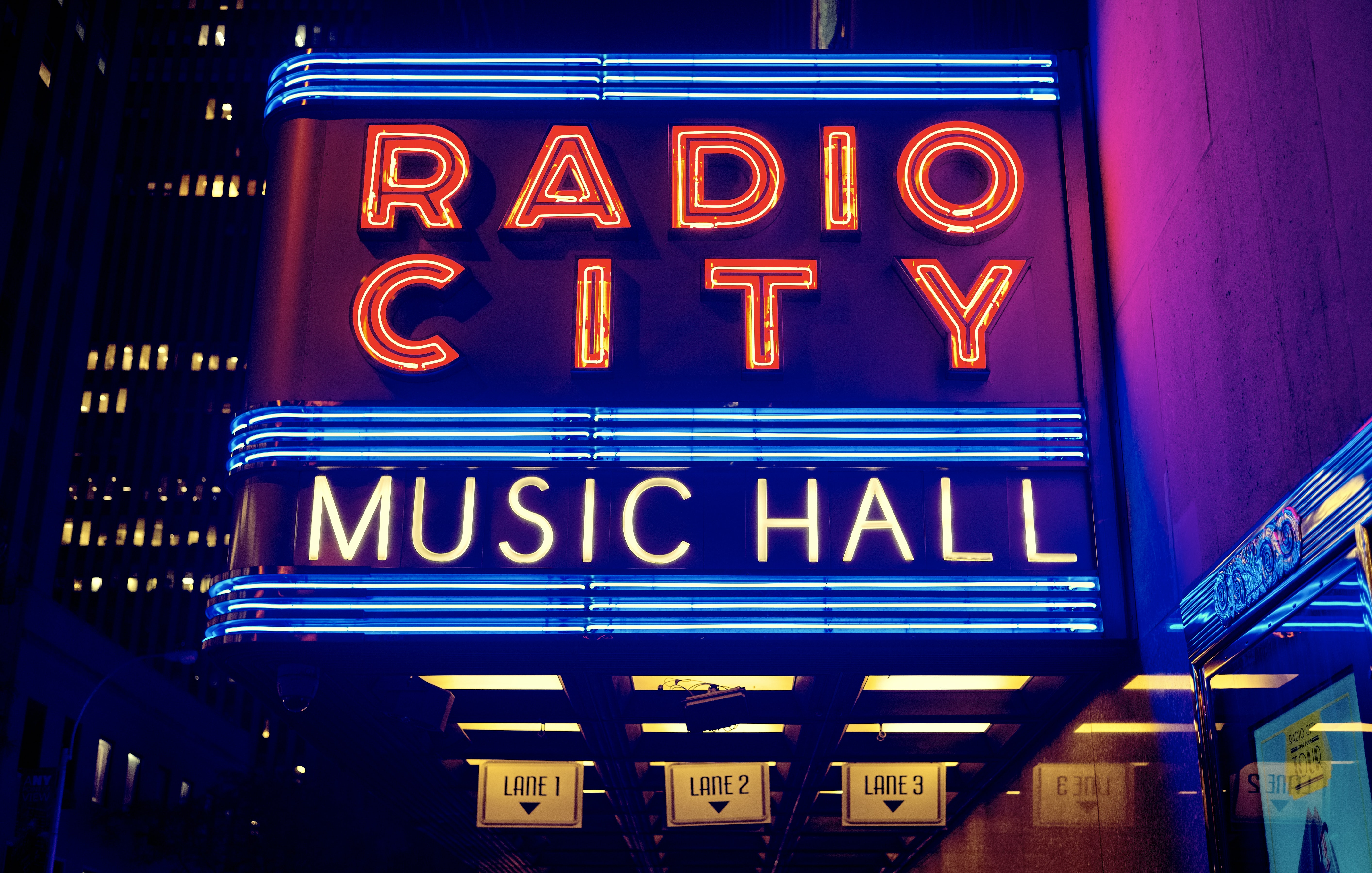 "A large neon sign reads ""Radio City Music Hall"""