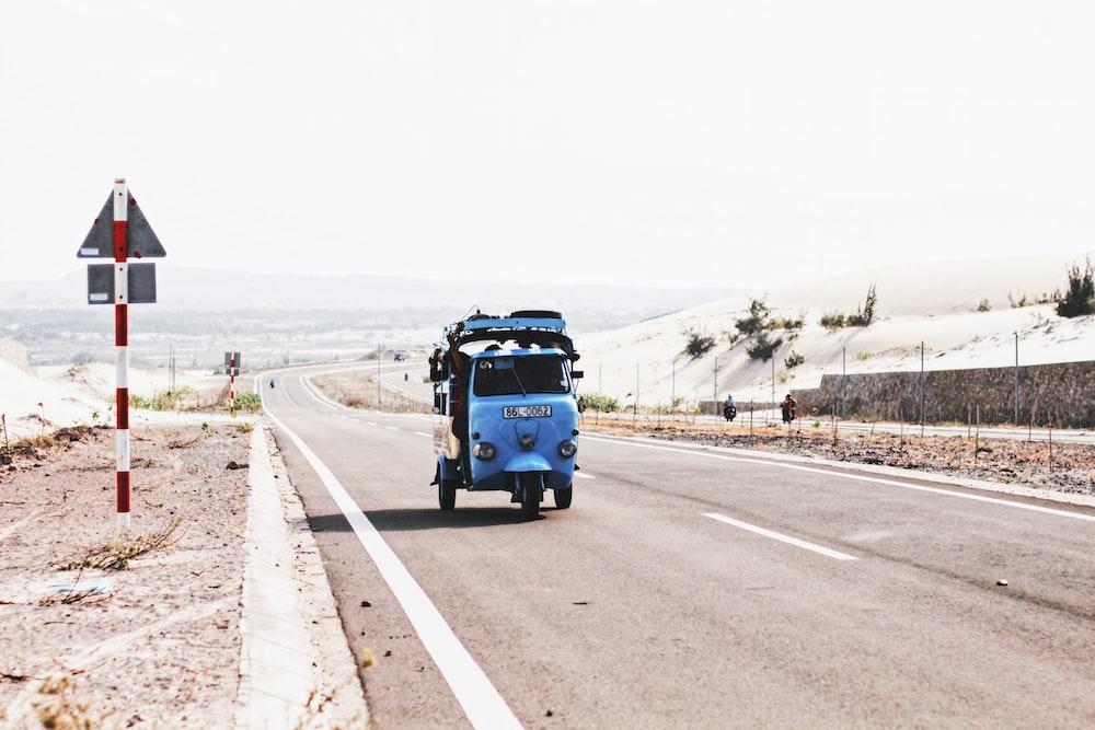 blue auto-rickshaw beside road signage
