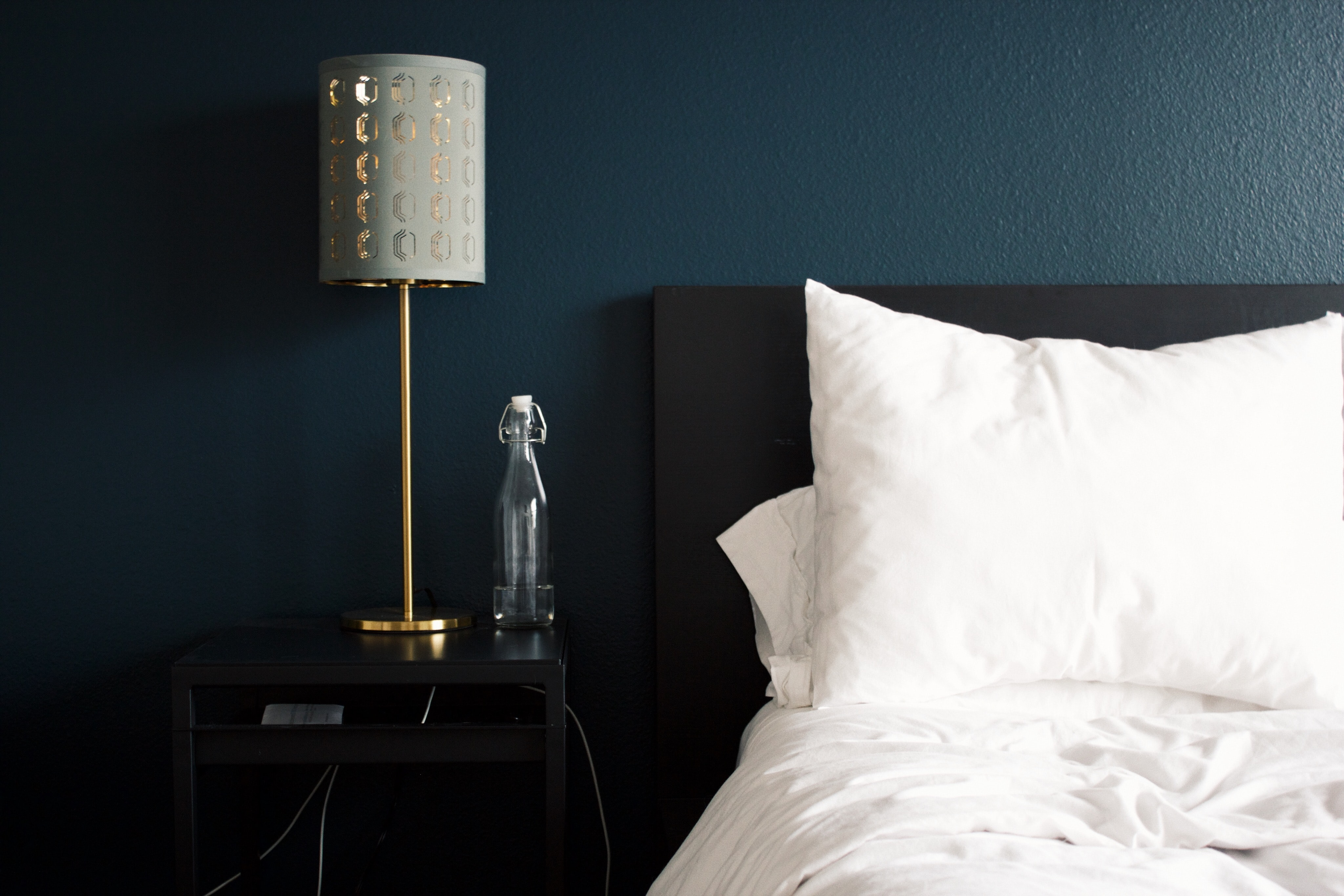 A white bed, silver lamp, empty carafe, blue wall, and a bedside table at Alta Yorktown Apartments