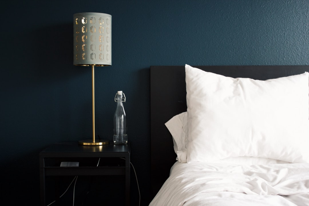 Hotel room with a bed, lamp and little silver figurine