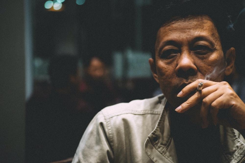 man smoking cigarette during nighttime